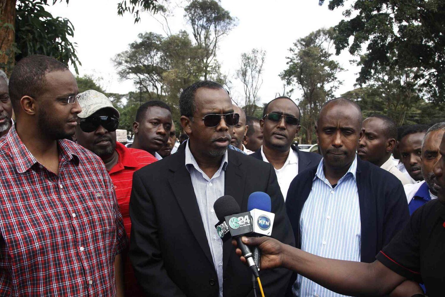 Somalia's ambassador to Kenya, Mohamed Ali Nur, centre,speaks to journalists during the burial of a 41-year-old Somali man and an 18-year-old Asian woman in Nairobi, Kenya Sunday. Both of them were killed during Saturday's mall shooting in Nairobi. (Khalil Senosi / The Associated Press)