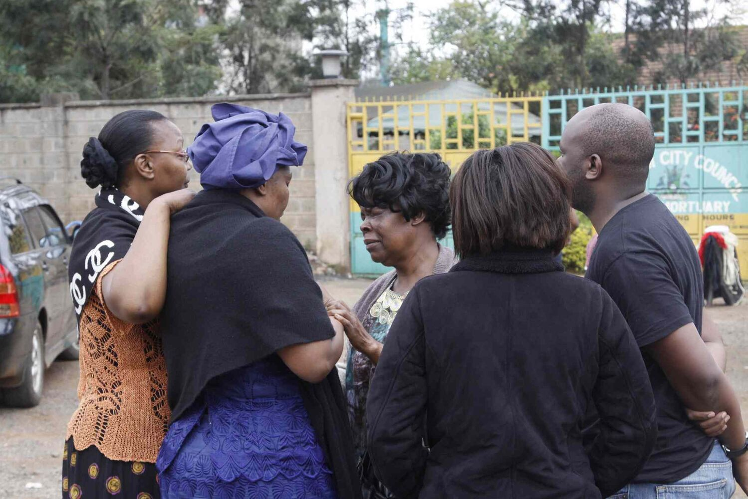 Relatives gather at  the Nairobi City Mortuary Sunday following the mall attack Saturday. Kenyan authorities said Islamic extremist attackers remain inside the upscale Kenyan shopping mall, holding an unknown number of hostages, after killing dozens and injuring 150. (Khalil Senosi / The Associated Press)
