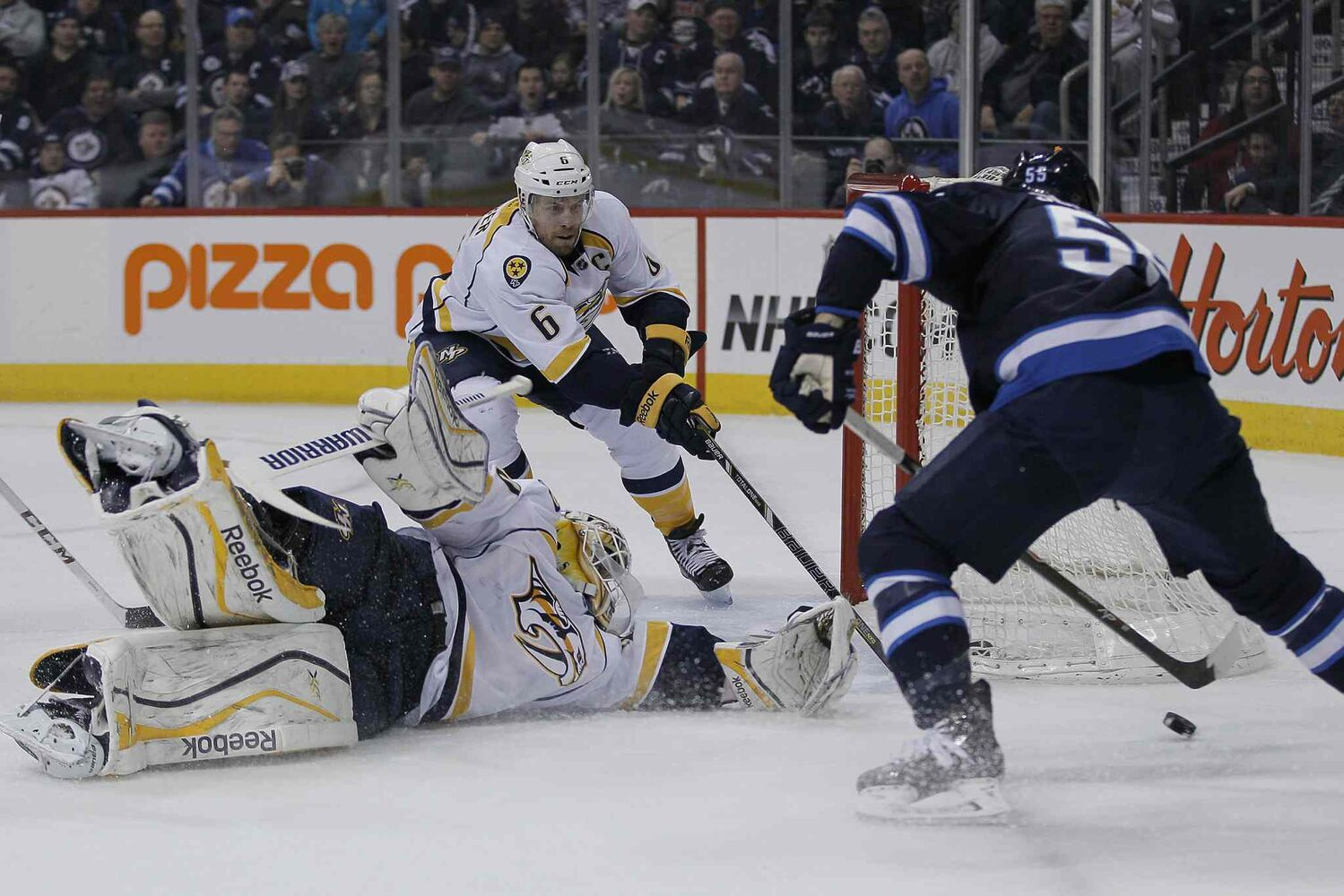 Winnipeg Jets' Mark Scheifele (55) gets around Nashville Predators' goaltender Carter Hutton (30) just before shooting the puck off Shea Weber (6) for the goal.