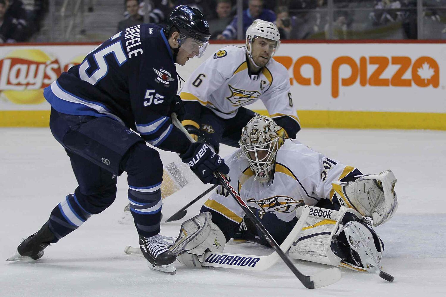 Winnipeg Jets' Mark Scheifele (55) gets around Nashville Predators' goaltender Carter Hutton (30) just before shooting the puck off of Shea Weber (6) for a second-period goal Tuesday.