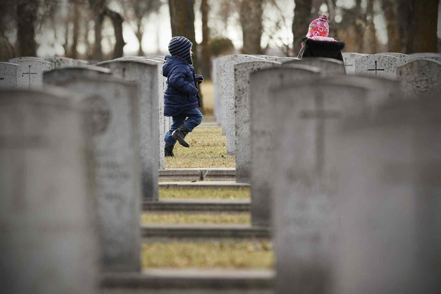 Children wander among the gravestones at Brookside Cemetery in Winnipeg on Remembrance Day.
