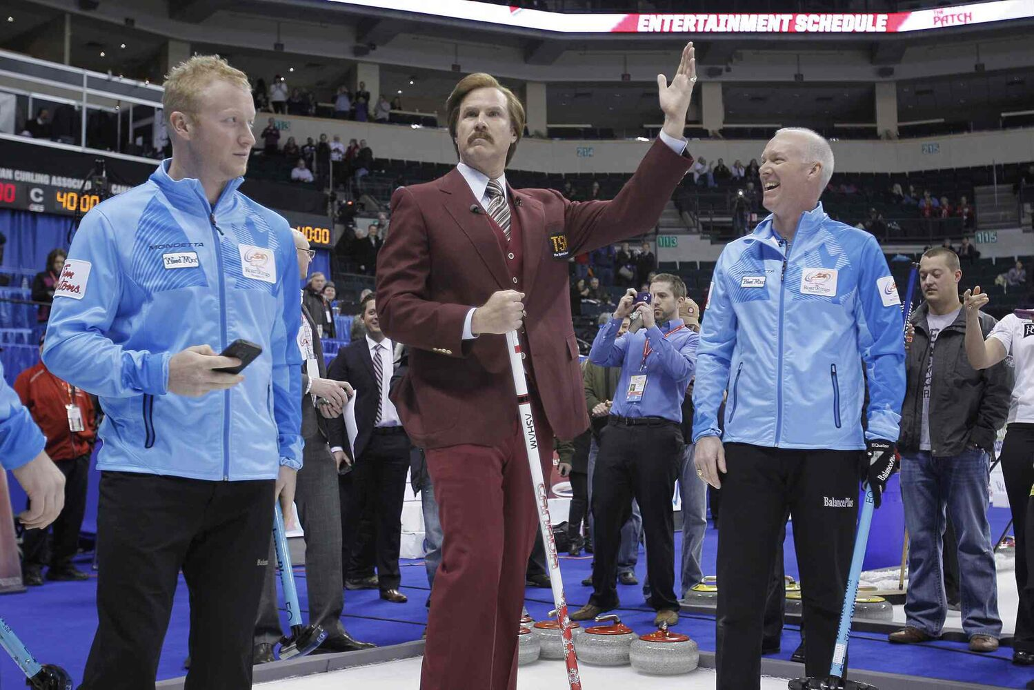 Burgundy celebrates after releasing a rock as Glenn Howard (right) and his team look on after opening ceremony.