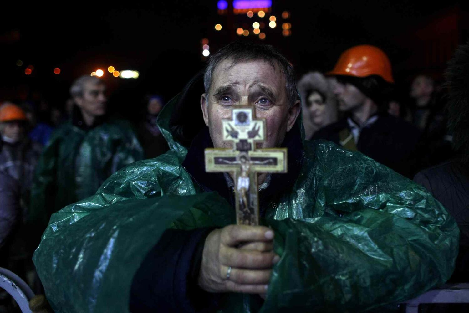 "An anti-government protester holds a crucifix as he prays at Independence Square in Kyiv, Ukraine. Ukraine's protest leaders and the president they aim to oust called a truce Wednesday, just hours after the military raised fears of a widespread crackdown with a vow to defeat ""terrorists"" responsible for seizing weapons and burning down buildings. (Marko Drobnjakovic / The Associated Press)"