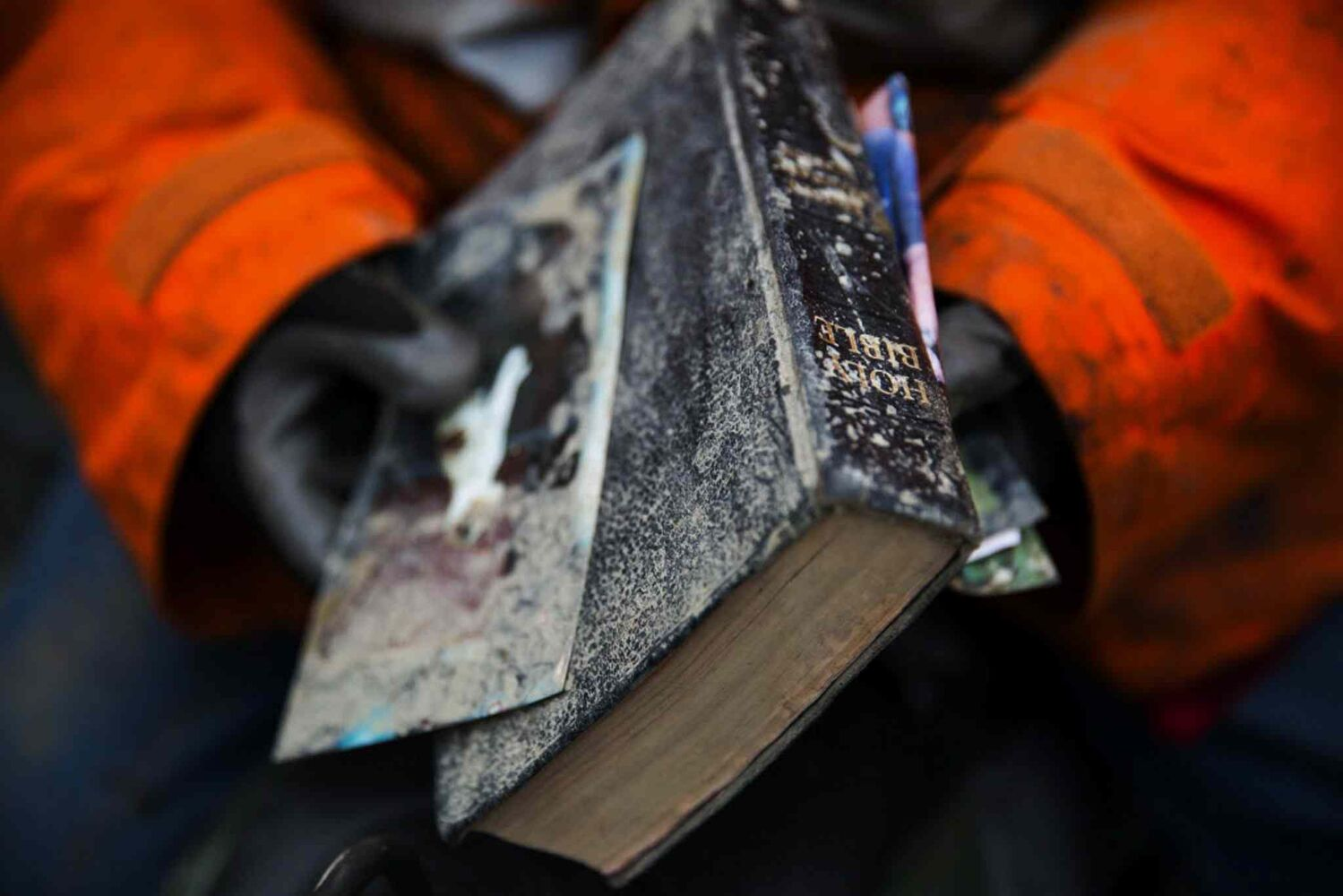 Elaine Young holds a bible pulled out of the debris field from the mudslide above the North Fork of the Stillaguamish River onto Highway 530, as recovery efforts are underway, near Oso, Wash.  (Marcus Yam / Seattle Times / MCT)