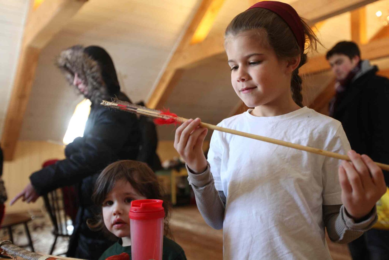 Eight-year-old Liam Greyeyes looks closely at a handcrafted arrow at as his little brother Alex looks on at one of the Festival du Voyageur workshops Saturday.    (Ruth Bonneville / Winnipeg Free Press)