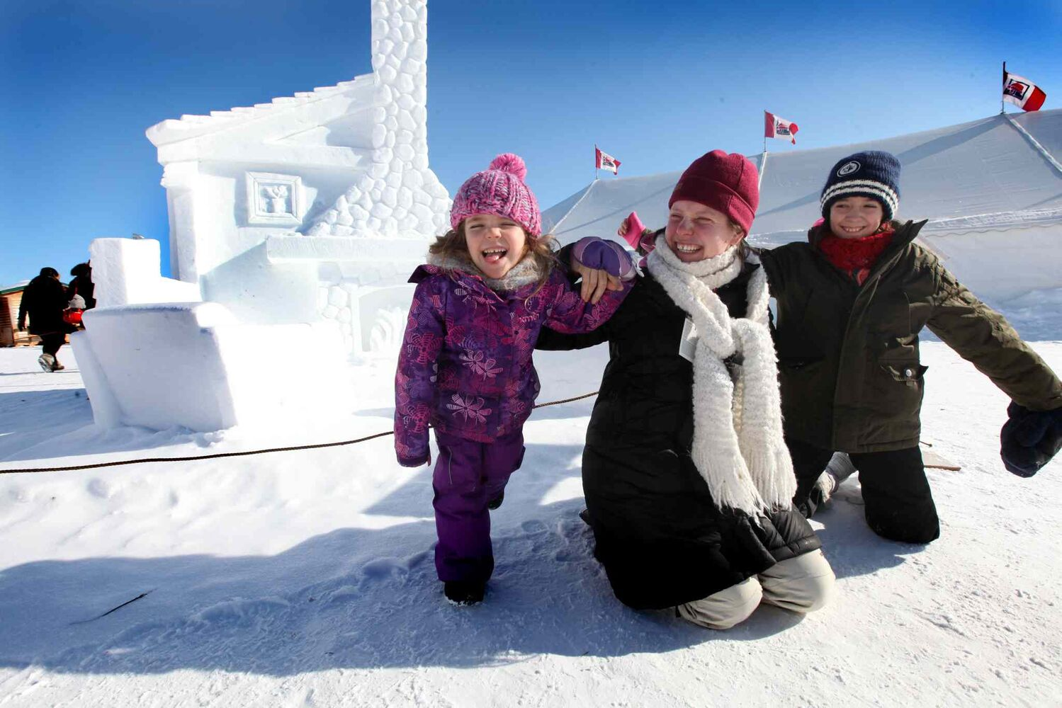 Five-year-old Monica Claire, her mom Elizabeth Whitaker-Jacques and her niece Tianna Govia,11, goof around near one of their favourite snow sculptures at Festival du Voyageur Saturday afternoon.  (Ruth Bonneville / Winnipeg Free Press)