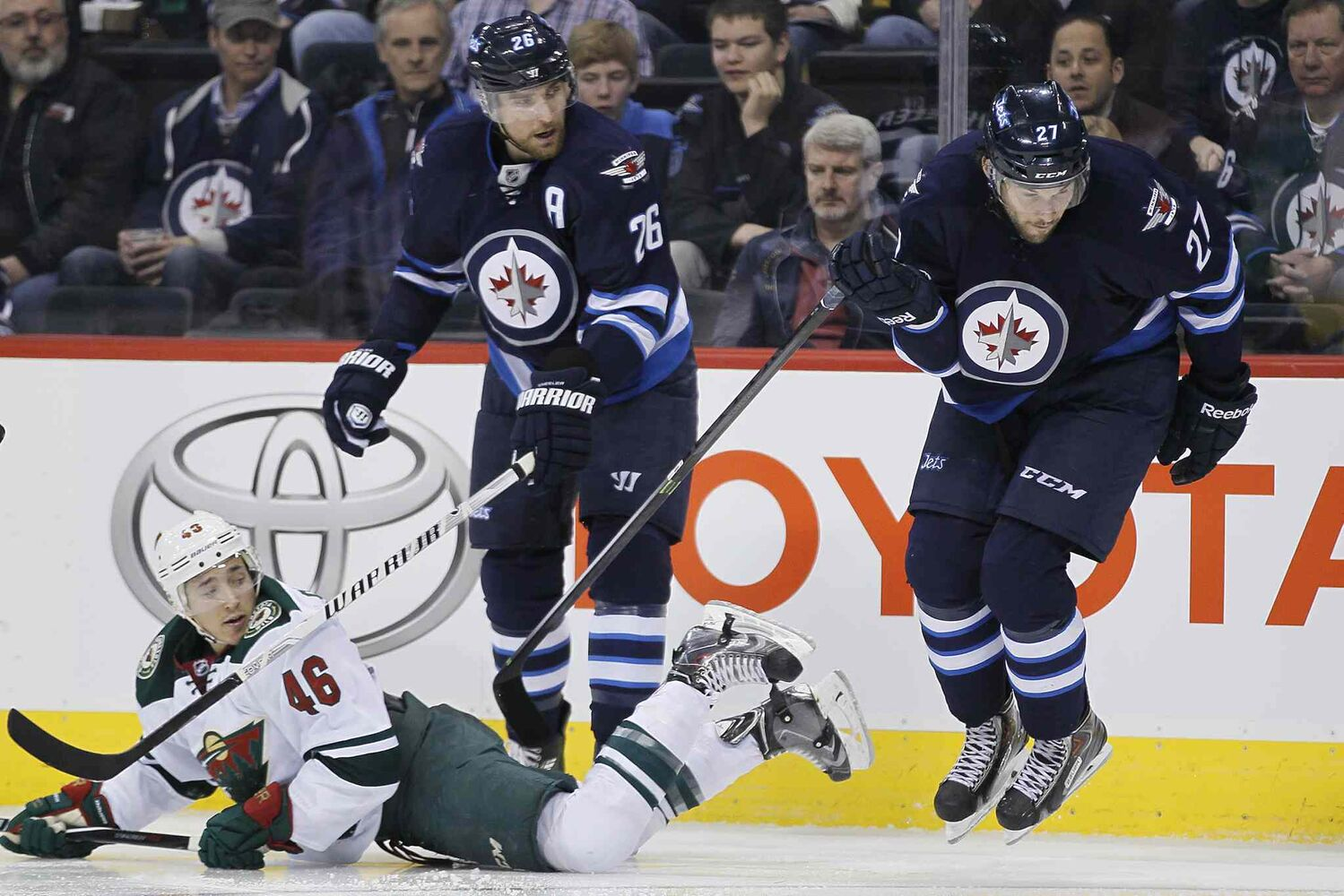 Jets forwards Blake Wheeler, left, and Eric Tangradi check Minnesota's Jared Spurgeon in the second period. (JOHN WOODS / WINNIPEG FREE PRESS)