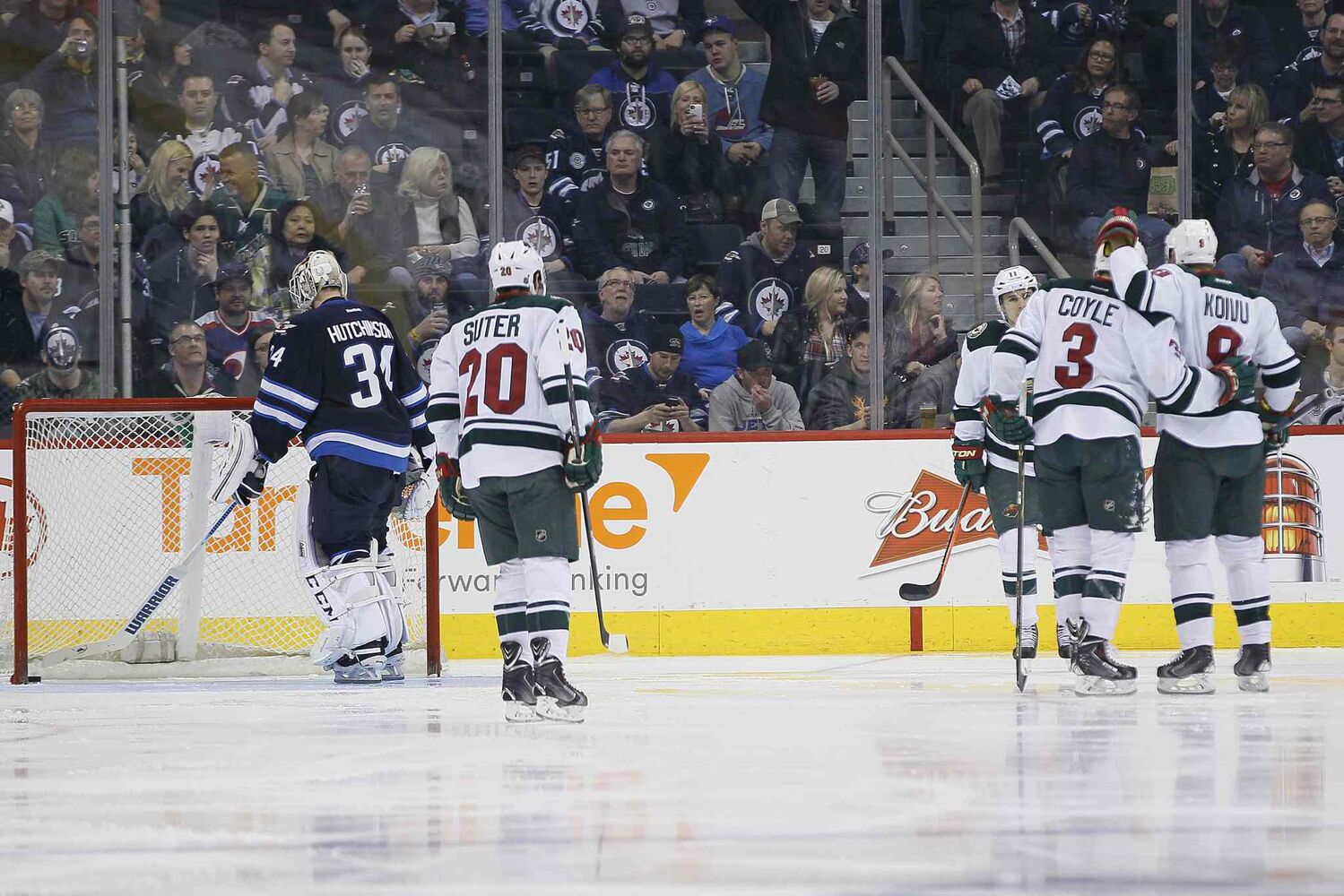 The Minnesota Wild's Ryan Suter (20), Zach Parise (11), Charlie Coyle (3) and Mikko Koivu (8) celebrate Coyle's goal as Winnipeg Jets goaltender Michael Hutchinson fishes the puck out of the net in the second period. (JOHN WOODS / WINNIPEG FREE PRESS)