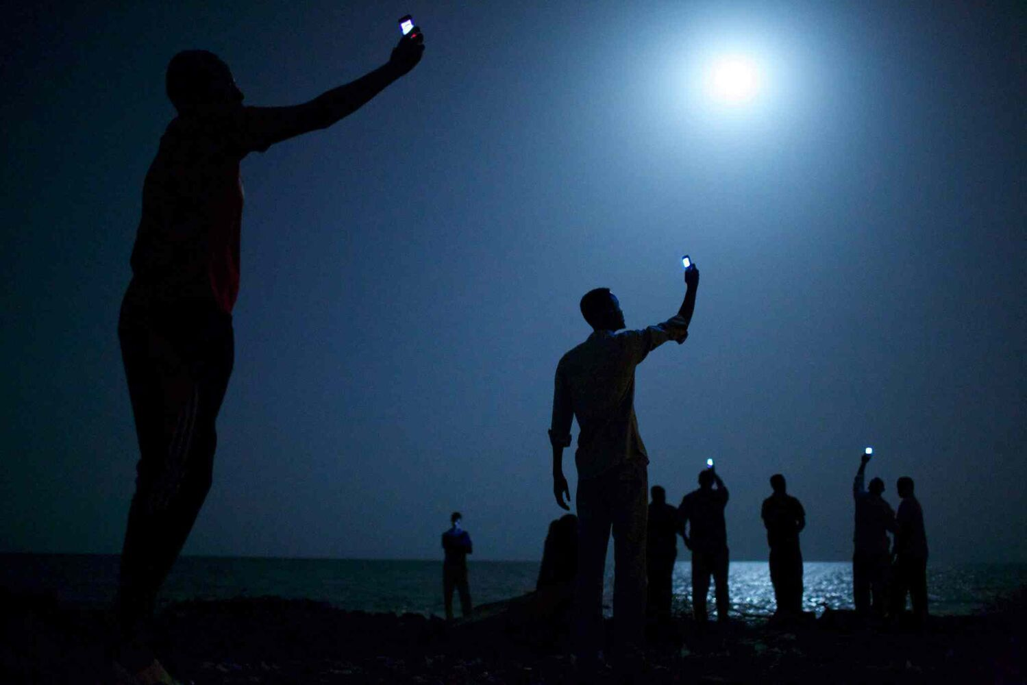 World Press Photo of the Year 2013 by John Stanmeyer of U.S.A.<p> African migrants on the shore of Djibouti city at night, raise their phones in an attempt to capture an inexpensive signal from neighbouring Somalia in Djibouti City, Djibouti on Feb. 26, 2013.  (John Stanmeyer, VII for National Geographic)