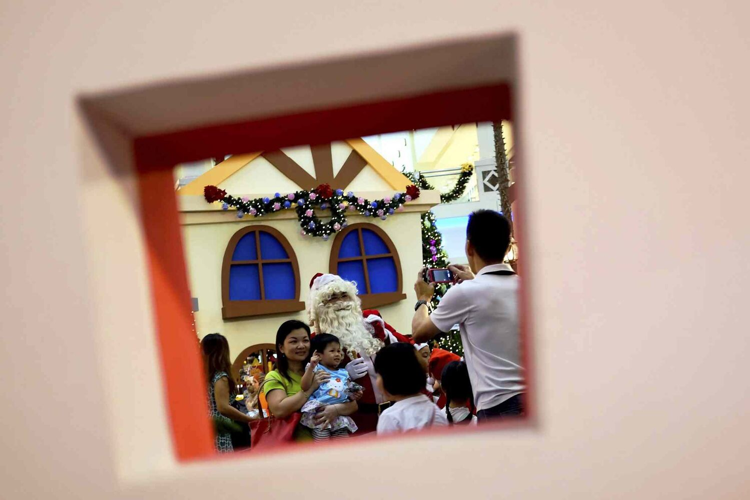 Shoppers pose for photos with a man in Santa Claus costume on Christmas Day at a shopping mall in Kuala Lumpur, Malaysia. (The Associated Press)