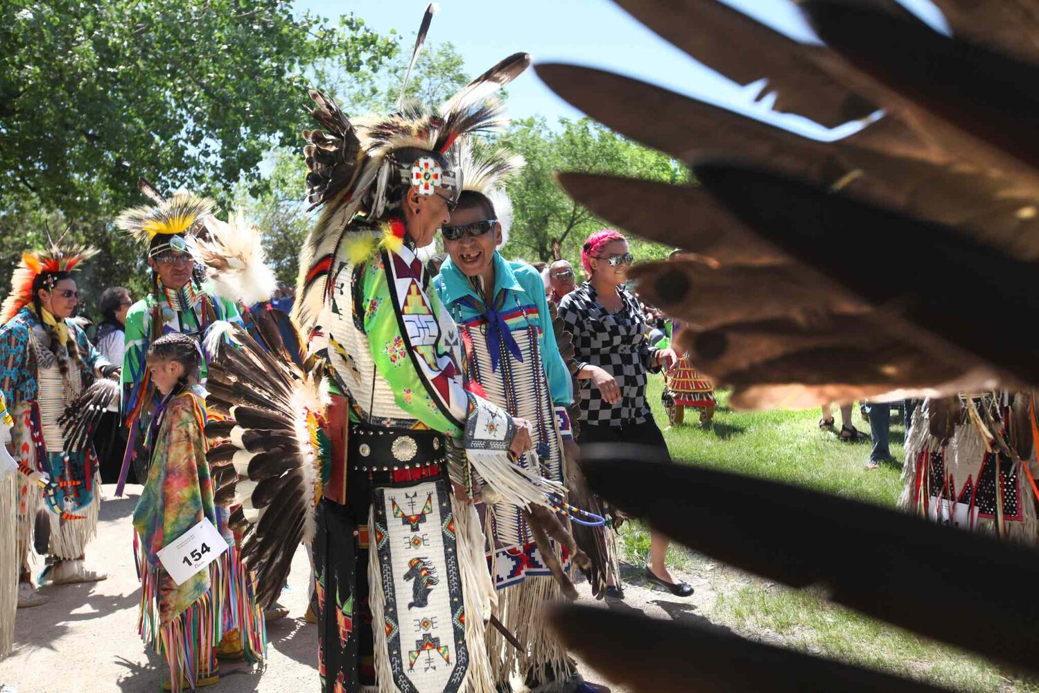 Dancers wait in line for the powwow's grand entry to begin. (Ruth Bonneville / Winnipeg Free Press)