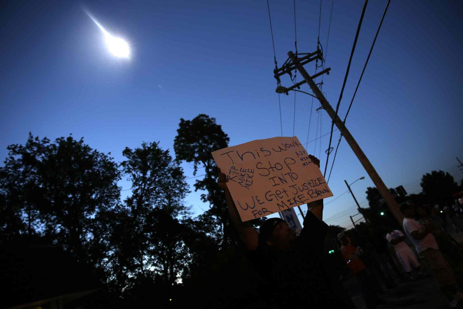 A protester holds up a sign as a police helicopter circles overhead Wednesday. (Jeff Roberson / The Associated Press)