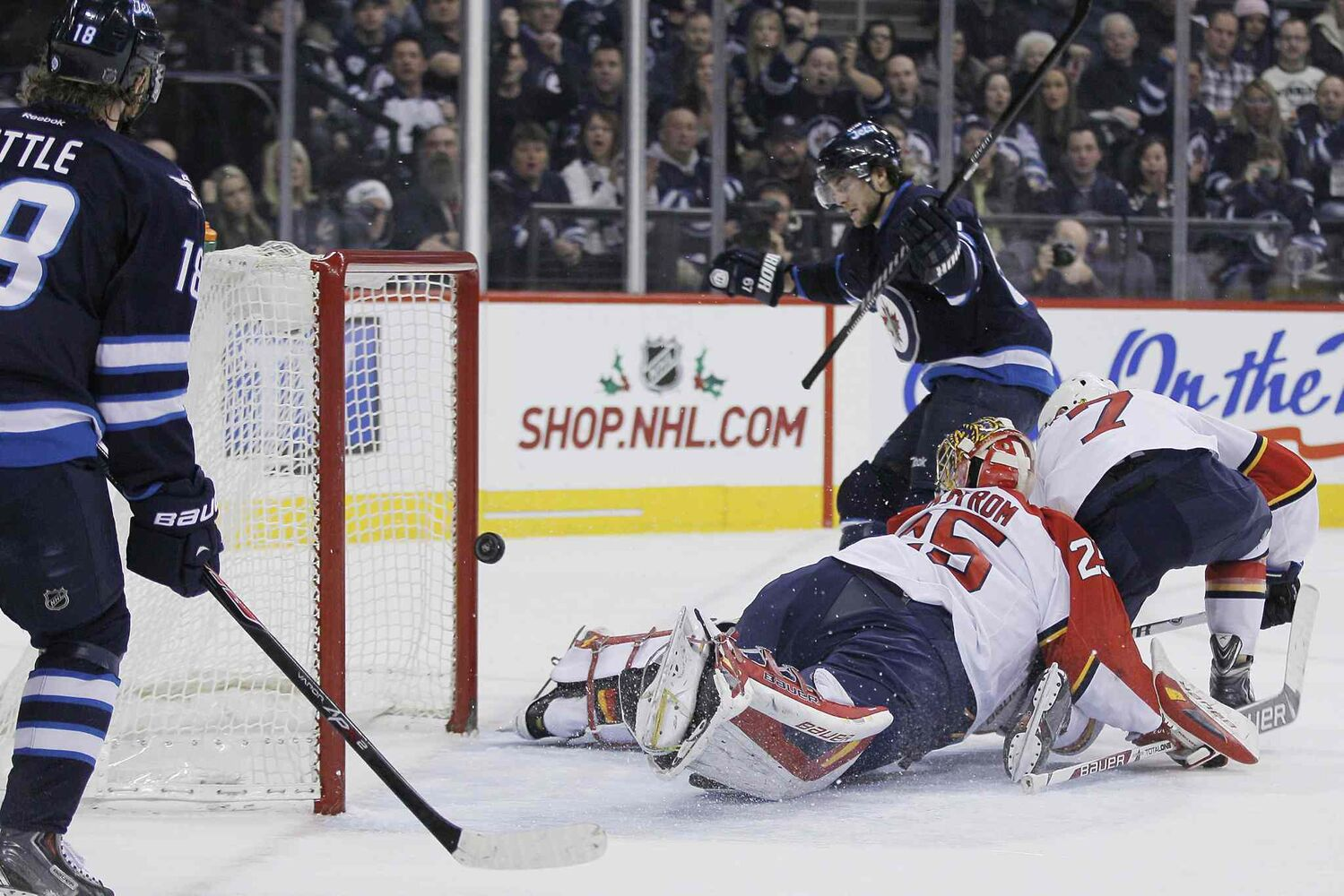 Winnipeg Jets' Michael Frolik (67) scores on Florida Panthers goaltender Jacob Markstrom (25) and Dmitry Kulikov (7) as Jets' Bryan Little (18) looks on during the second period. (John Woods  The Canadian Press)