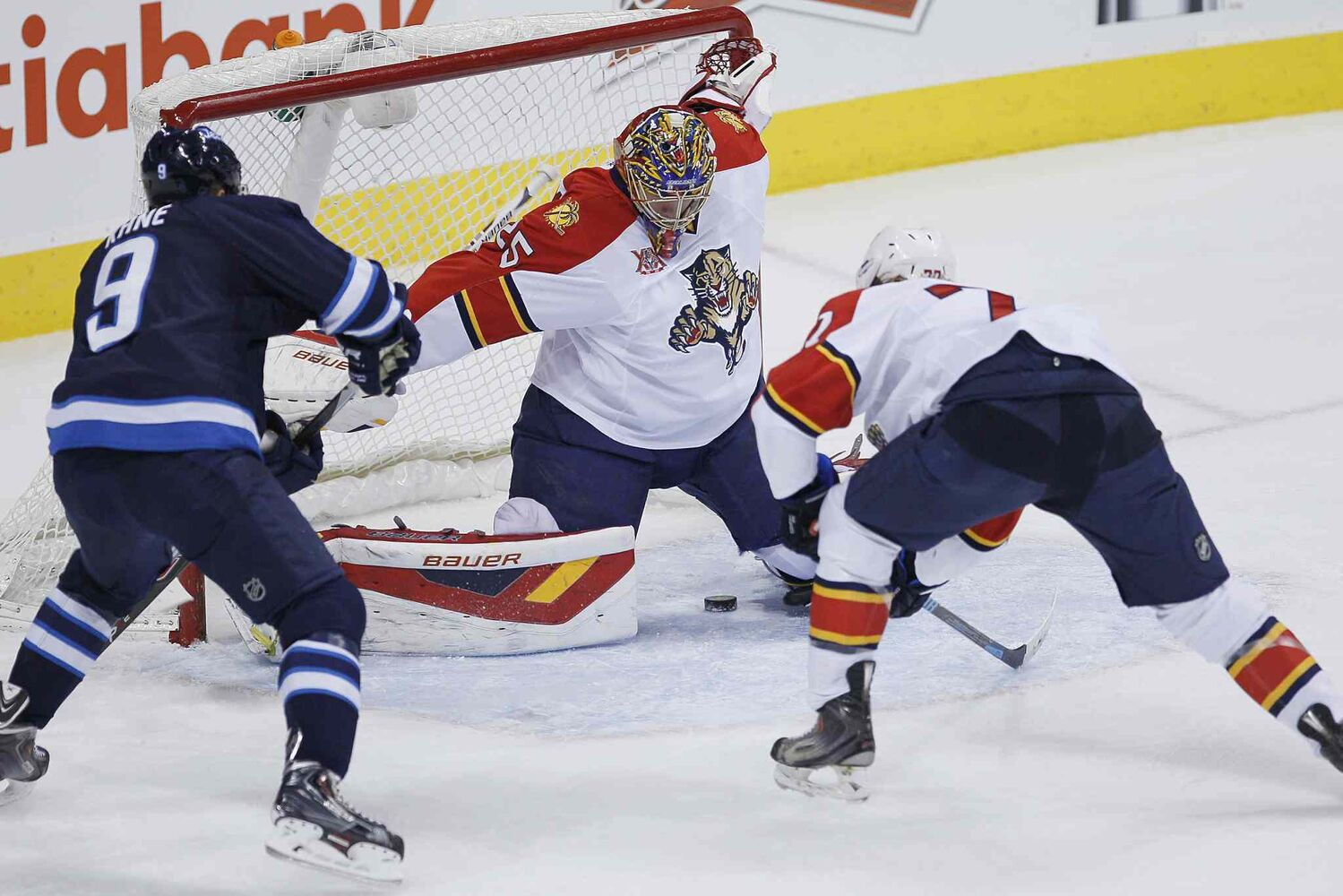 Florida Panthers' Tom Gilbert (77) tips the shot by Winnipeg Jets' Jacob Trouba (8) through the legs of goaltender Jacob Markstrom (25) as Jets' Evander Kane (9) looks on during the first period.
