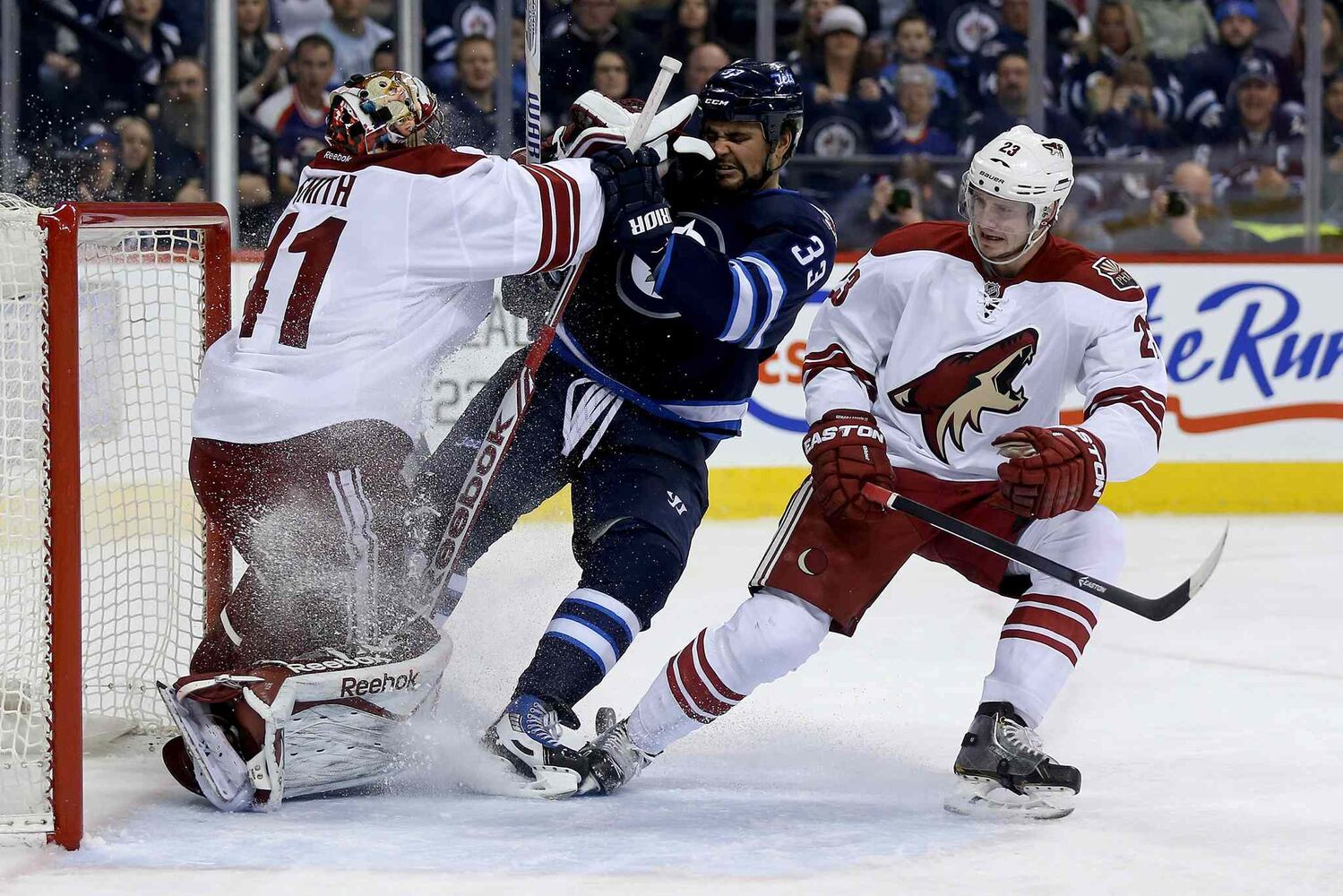 Jets forward Dustin Byfuglien crashes the Phoenix net and Coyotes goaltender Mike Smith, who gives Byfuglien a shot in the face. (TREVOR HAGAN / WINNIPEG FREE PRESS)