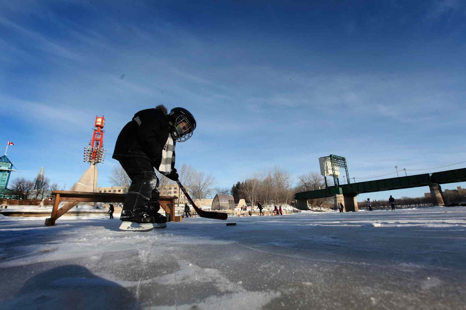Four-year-old Jack Springer didn't seem to mind the cold as he played hockey on the new rink on the Assiniboine River Thursday with his dad.   (Ruth Bonneville / Winnipeg Free Press)