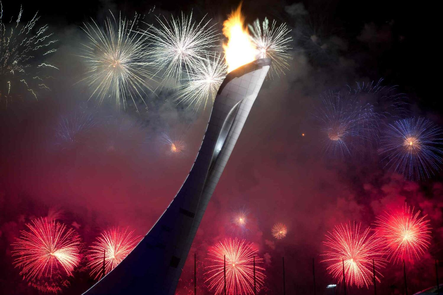 Fireworks explode behind the Olympic torch after it was lit at end of the opening ceremony for the 2014 Winter Olympics in Sochi, Russia, Friday, Feb. 7, 2014. (AP Photo/Bernat Armangue)
