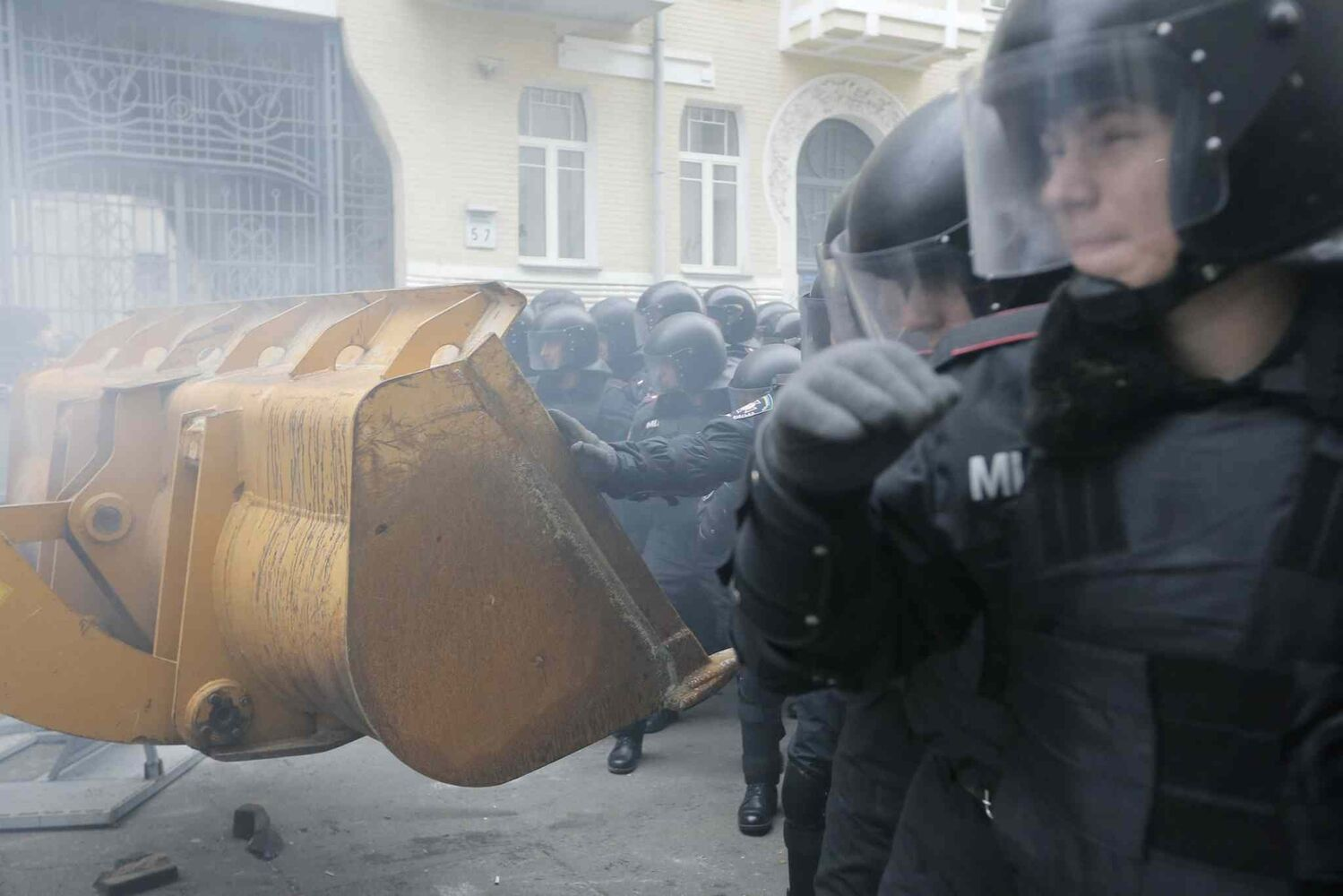 Protesters use an excavator during clashes with police at the Presidential office in Kiev, Ukraine, on Sunday. As many as 100,000 demonstrators chased away police to rally in the center of Ukraine's capital on Sunday, defying a government ban on protests on Independence Square, in the biggest show of anger over the president's refusal to sign an agreement with the European Union. (Efrem Lukatsky / The Associated Press)