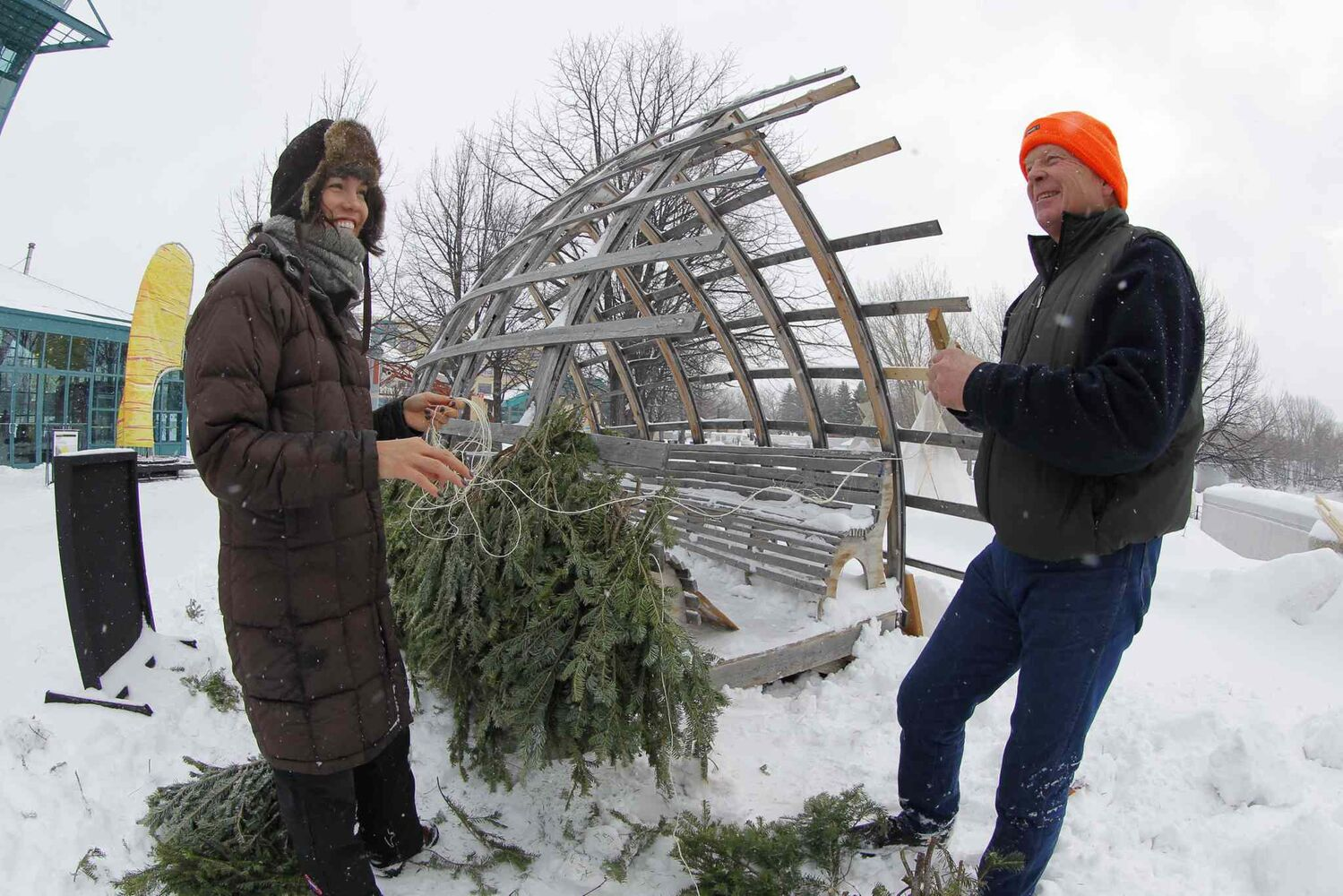 Hut designers Mamie Griffith and Richard Kroeker assemble Kroeker's 2010 winning hut design, Fir Hut, at the Forks on Friday.  (Boris Minkevich / Winnipeg Free Press)