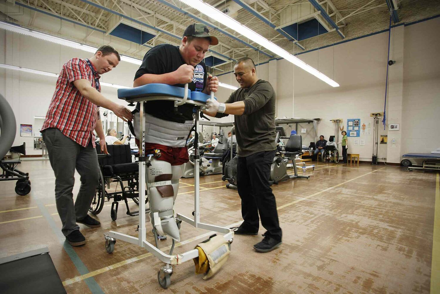 "Cole Maydanuk walks with his practice ""tomato cage"" legs and works with his therapist Ron Recuencoat during a physiotherapy session at HSC.