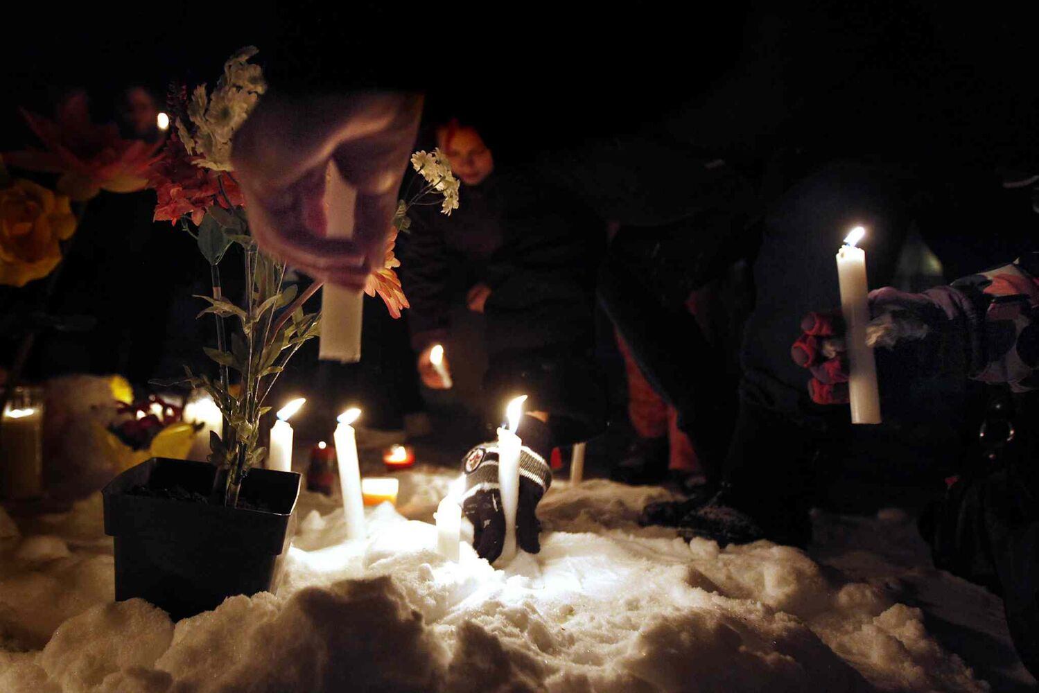 Friends and family place candles in the snow at a vigil for Nadia Fiddler in the courtyard of a Manitoba Housing complex on Doncaster Sunday, January 25, 2013. Although not confirmed by police, it is alleged that Fiddler was found dead in the courtyard Saturday.