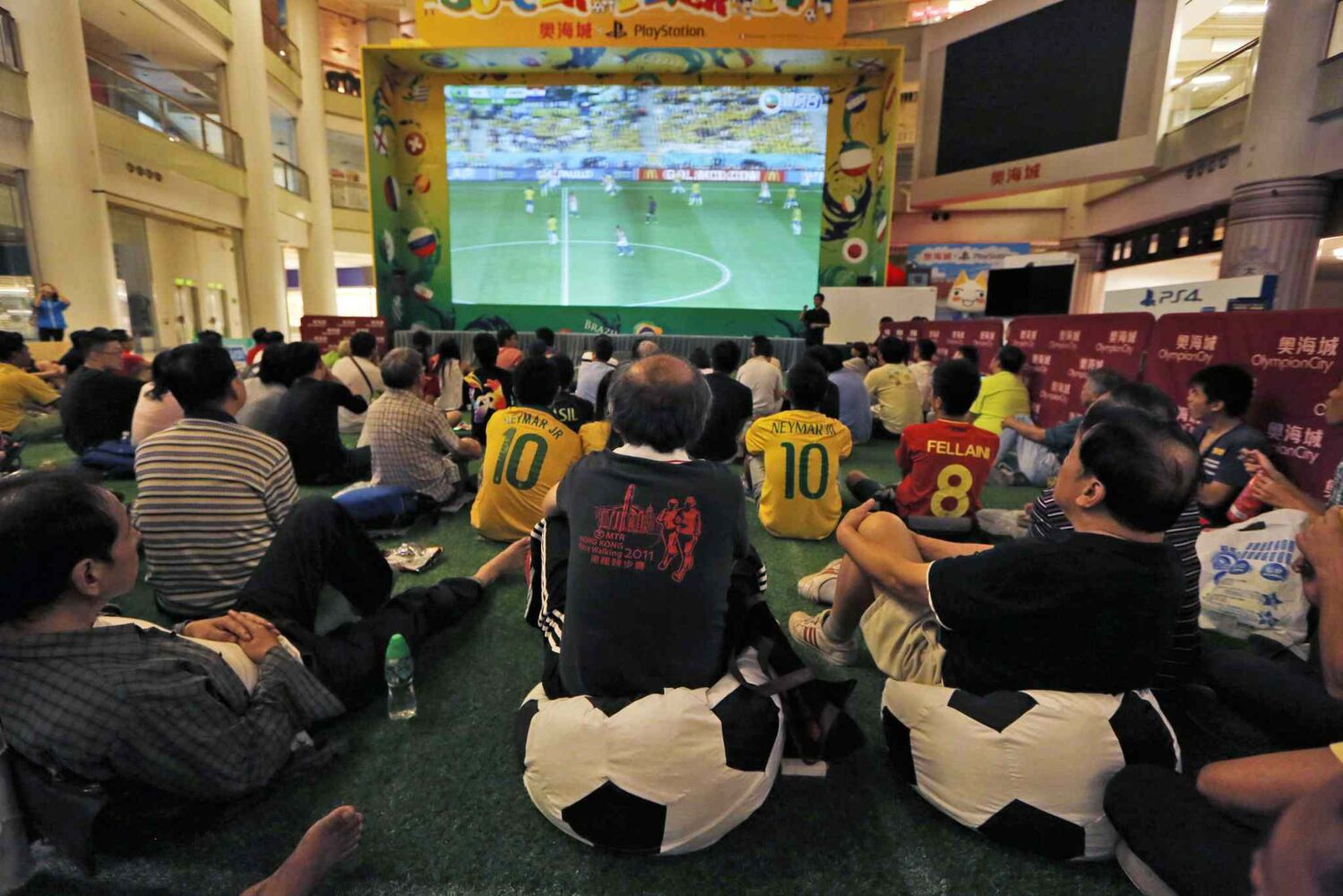 Soccer fans watch the opening match of the 2014 World Cup between Brazil and Croatia at a shopping mall in Hong Kong on Friday, June 13, 2014. (local time) (Kin Cheung / The Associated PRess)