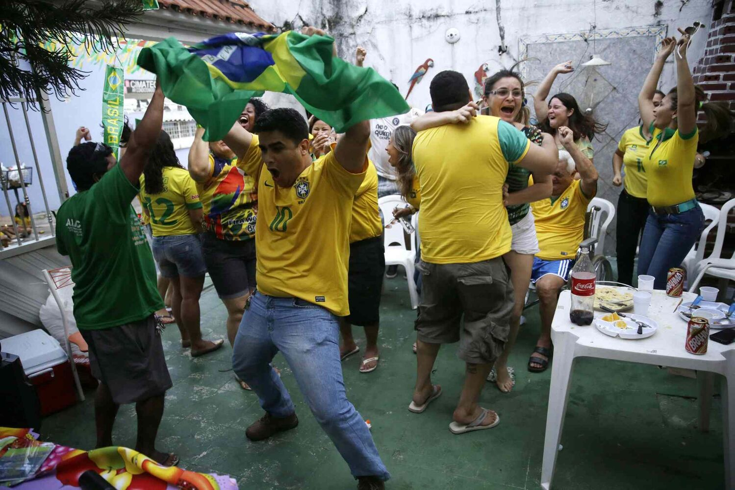 Soccer fans celebrate on the patio of a private residence as they watch a live broadcast of the goal scored by Brazilian midfielder Oscar dos Santos Emboaba Júnior in the World Cup opening match against Croatia, in Manaus, Brazil, Thursday, June 12, 2014. Brazil defeated Croatia 3-1. Oscar scored the third goal.  (Martin Mejia / The Associated Press)