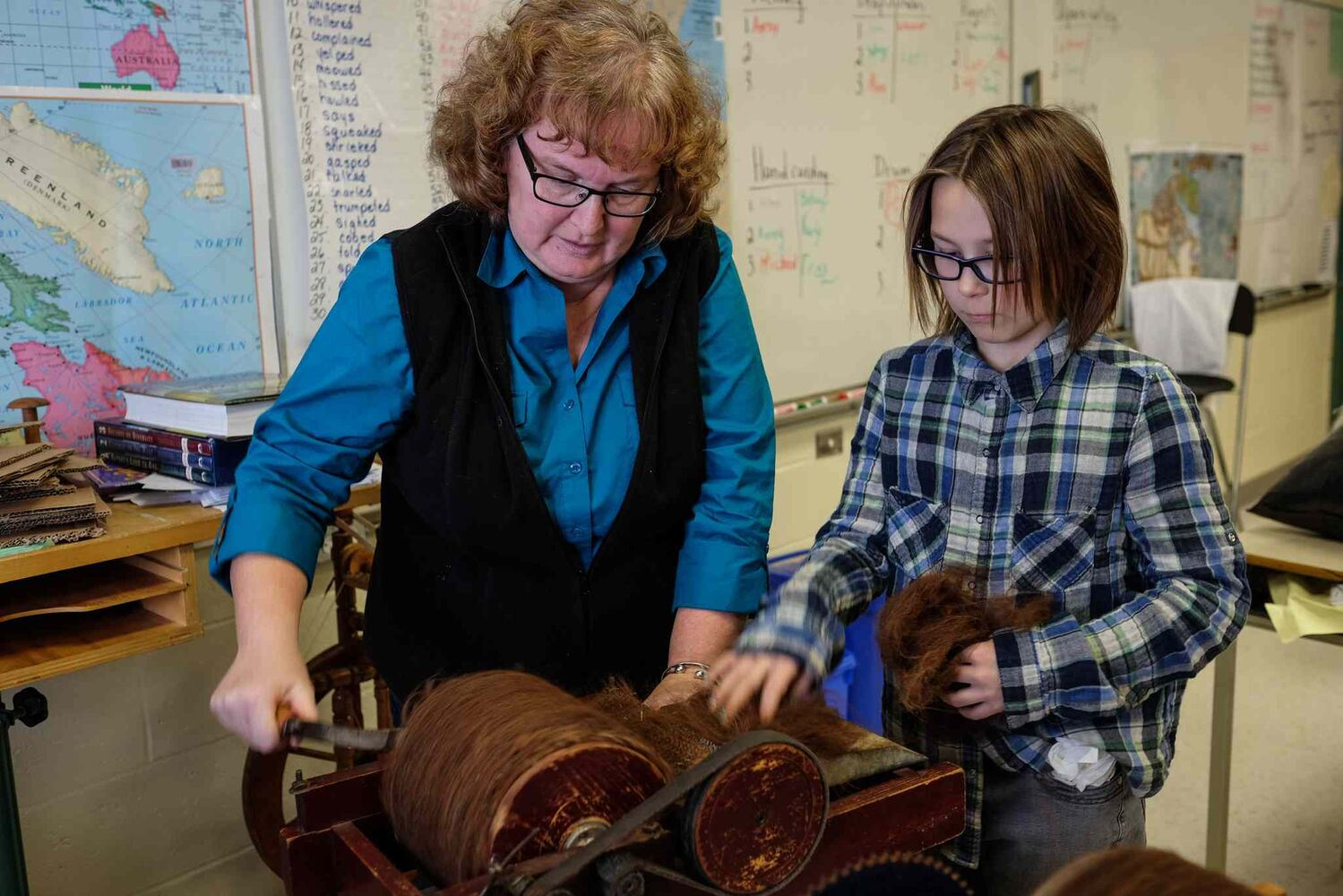 Teacher Elaine Owen helps student Kezia Swain, 11, with one of the drum carding machines.  (MIKE DEAL / WINNIPEG FREE PRESS)