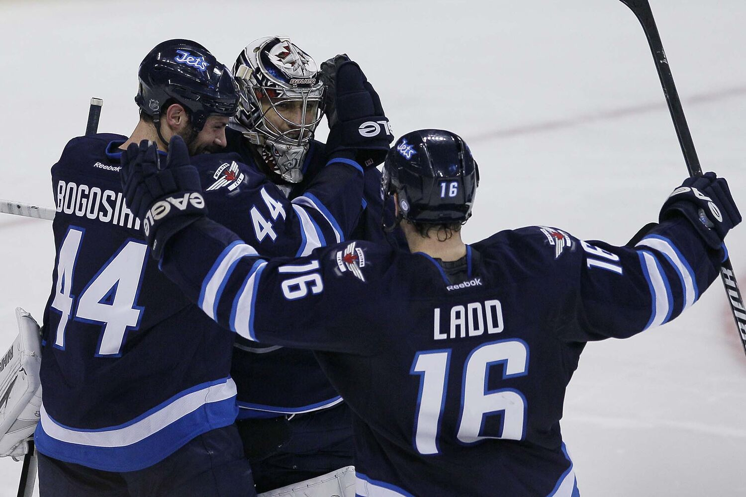 Winnipeg Jets' Zach Bogosian (44), goaltender Ondrej Pavelec (31) and Andrew Ladd (16)¤celebrate their NHL win over the over San Jose Sharks in penalty shots. (JOHN WOODS / WINNIPEG FREE PRESS)
