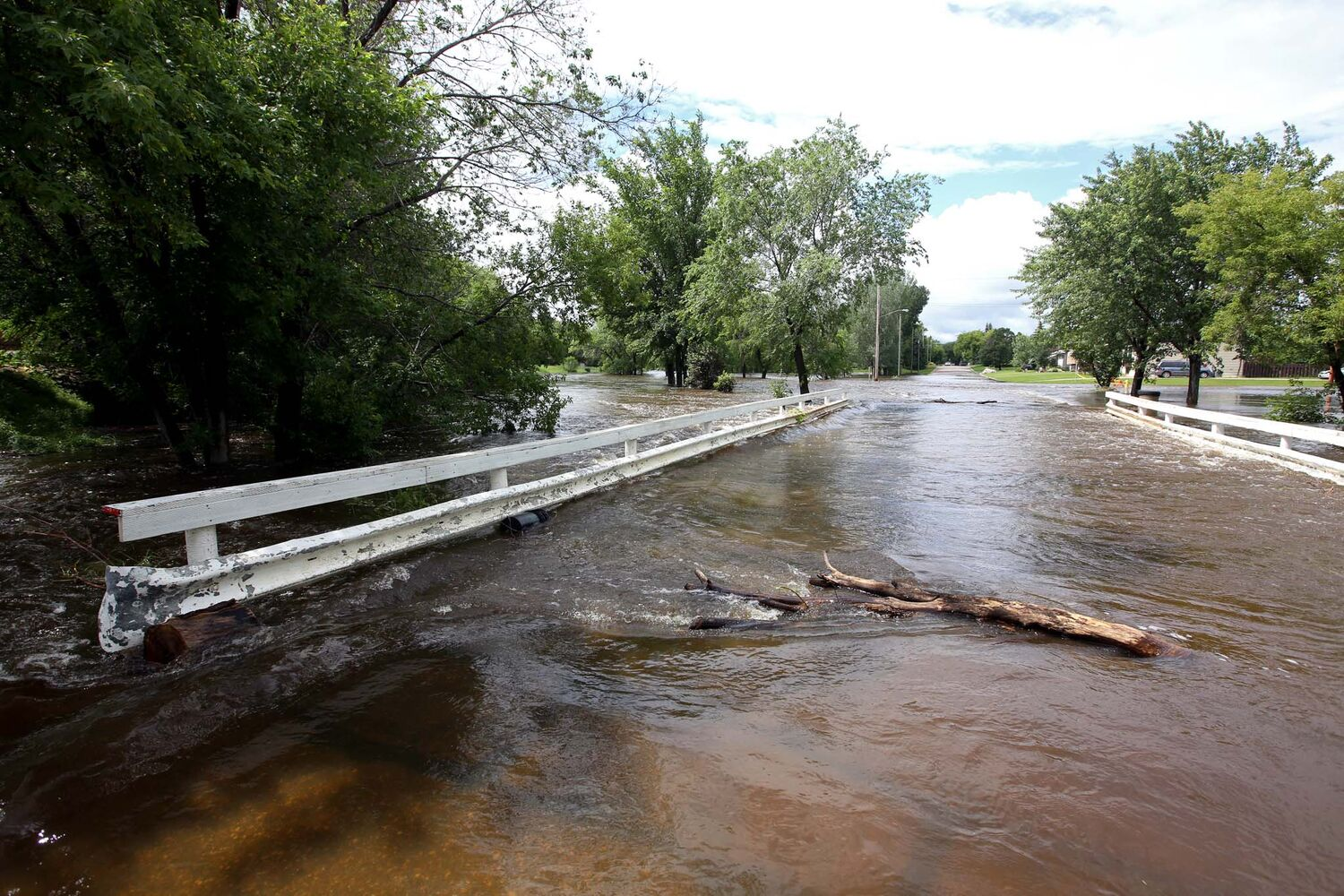 The swollen Gopher Creek in the town of Virden flows over a bridge on Monday.