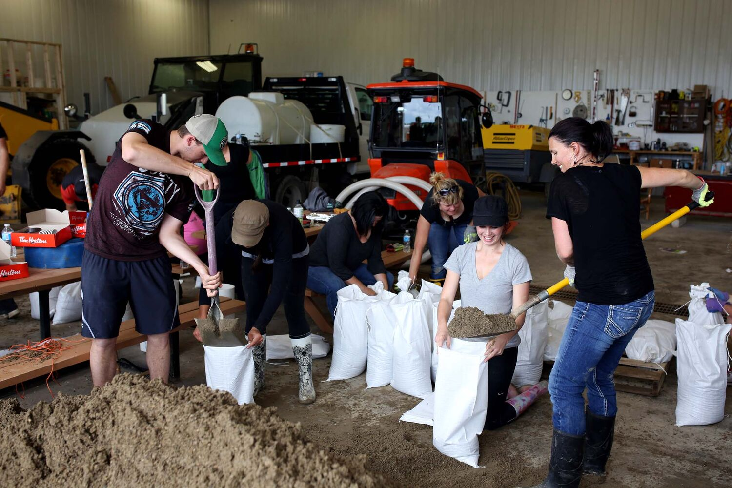 Volunteers make sandbags at the public works building in Virden during flood fighting efforts on Monday afternoon.