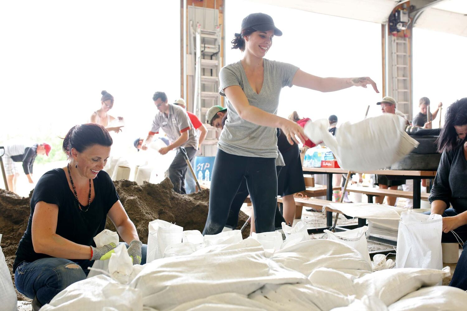Volunteers Kyla Martens and Brooke Williams make sandbags at the public works building in Virden during flood fighting efforts on Monday afternoon.  (Tim Smith / Brandon Sun)