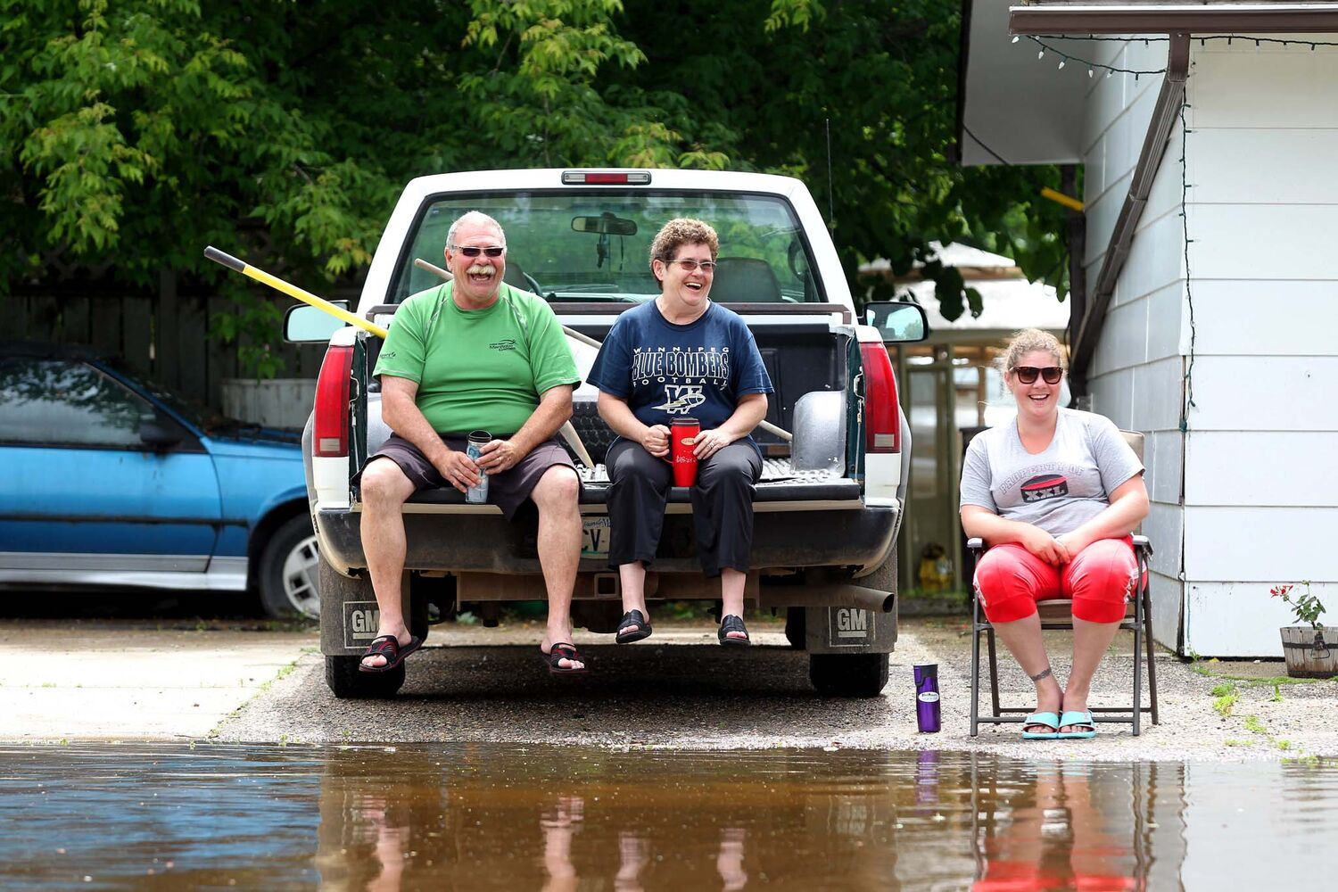 Bill Hayward, his wife Brenda and daughter Carly watch the water from the swollen Gopher Creek slowly rise in front of their home on King Street in Virden on Monday afternoon.  (Tim Smith / Brandon Sun)