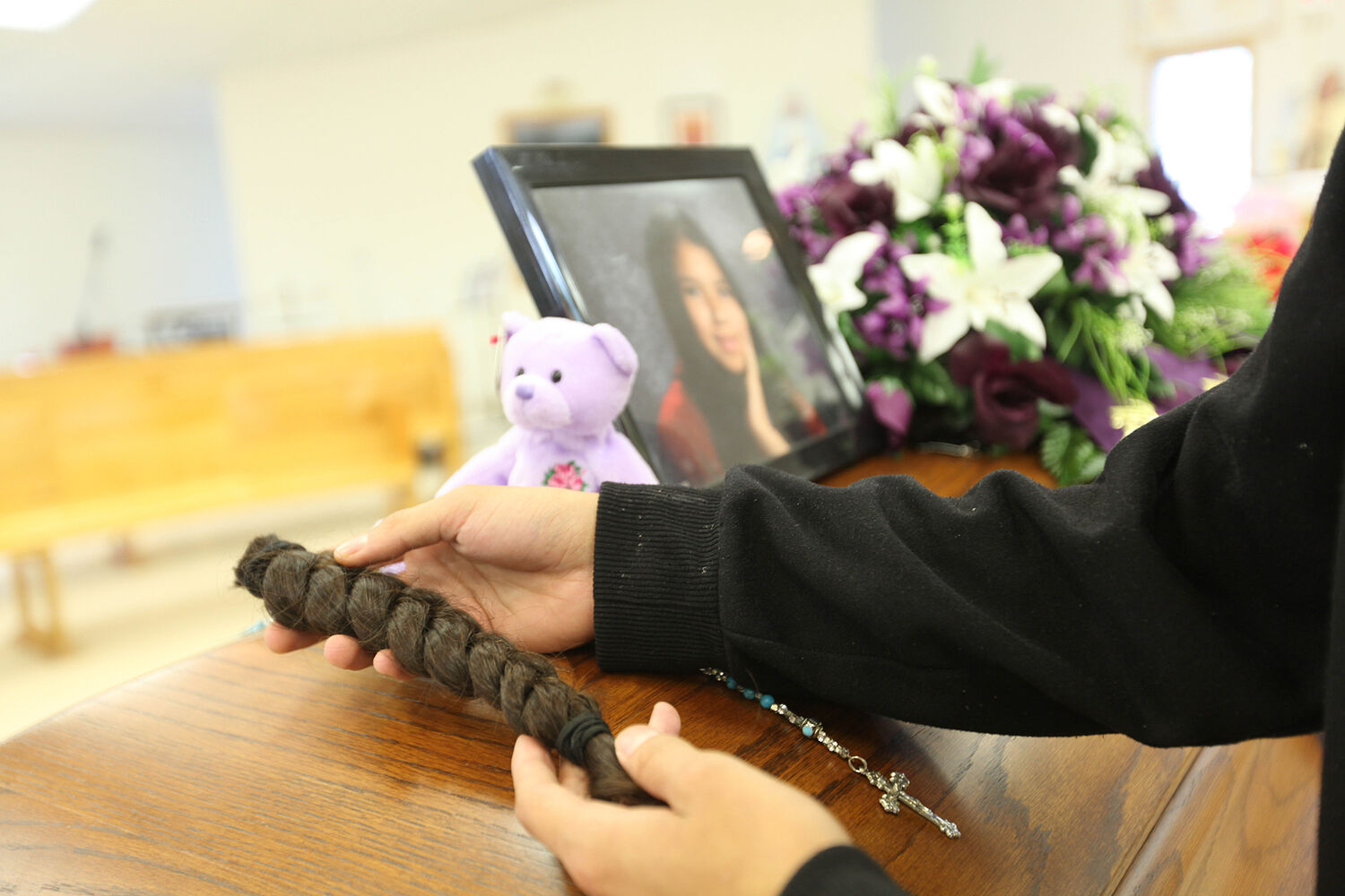 Tina Fontaine's older brother Dillion St. Paul is grief stricken as spends some final moments with his little sister's casket after her funeral in Sagkeeng First Nation.  During the service Dillion St. Paul cut off his braided ponytail and left it on her casket as part of a native family tradition.