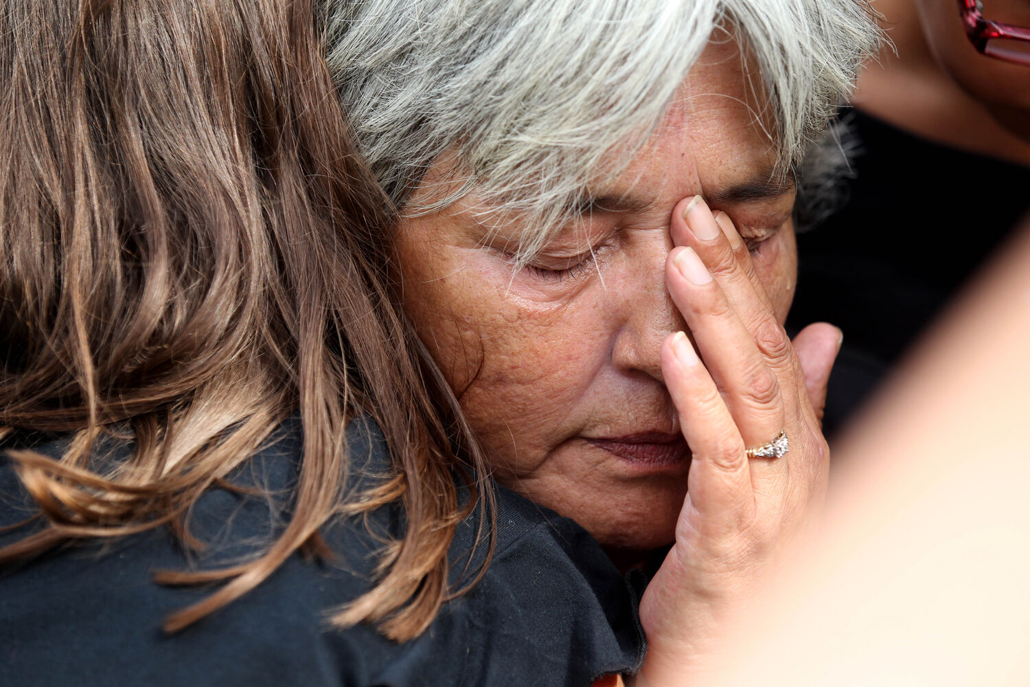 Thelma Favel is comforted by her niece Katie-Lee Fontaine while her deceased grandniece, Tina Fontaine was taken away in a hearse at Sagkeeng First Nation following her funeral Saturday.   (Ruth Bonneville / The Winnipeg Free Press)