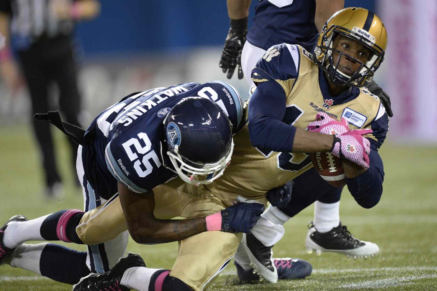 Winnipeg Blue Bombers' Jake Killeen is stopped by Toronto Argonauts' Pat Watkins during the first quarter.