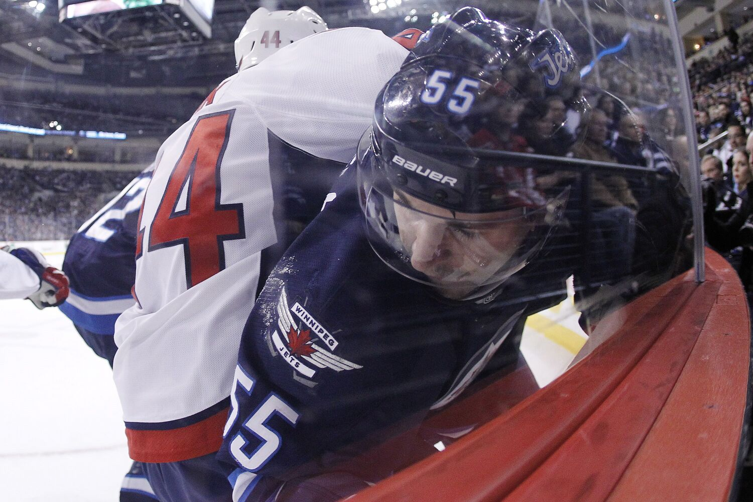 Mark Scheifele is pinned against the boards by Washington's Brooks Orpik. (John Woods / The Canadian Press)