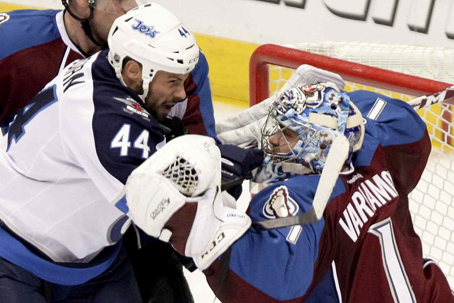 Winnipeg Jets defenceman  Zach Bogosian gets tangled up with Colorado Avalanche goalie Semyon Varlamov during the first period. (BARRY GUTIERREZ / THE ASSOCIATED PRESS)