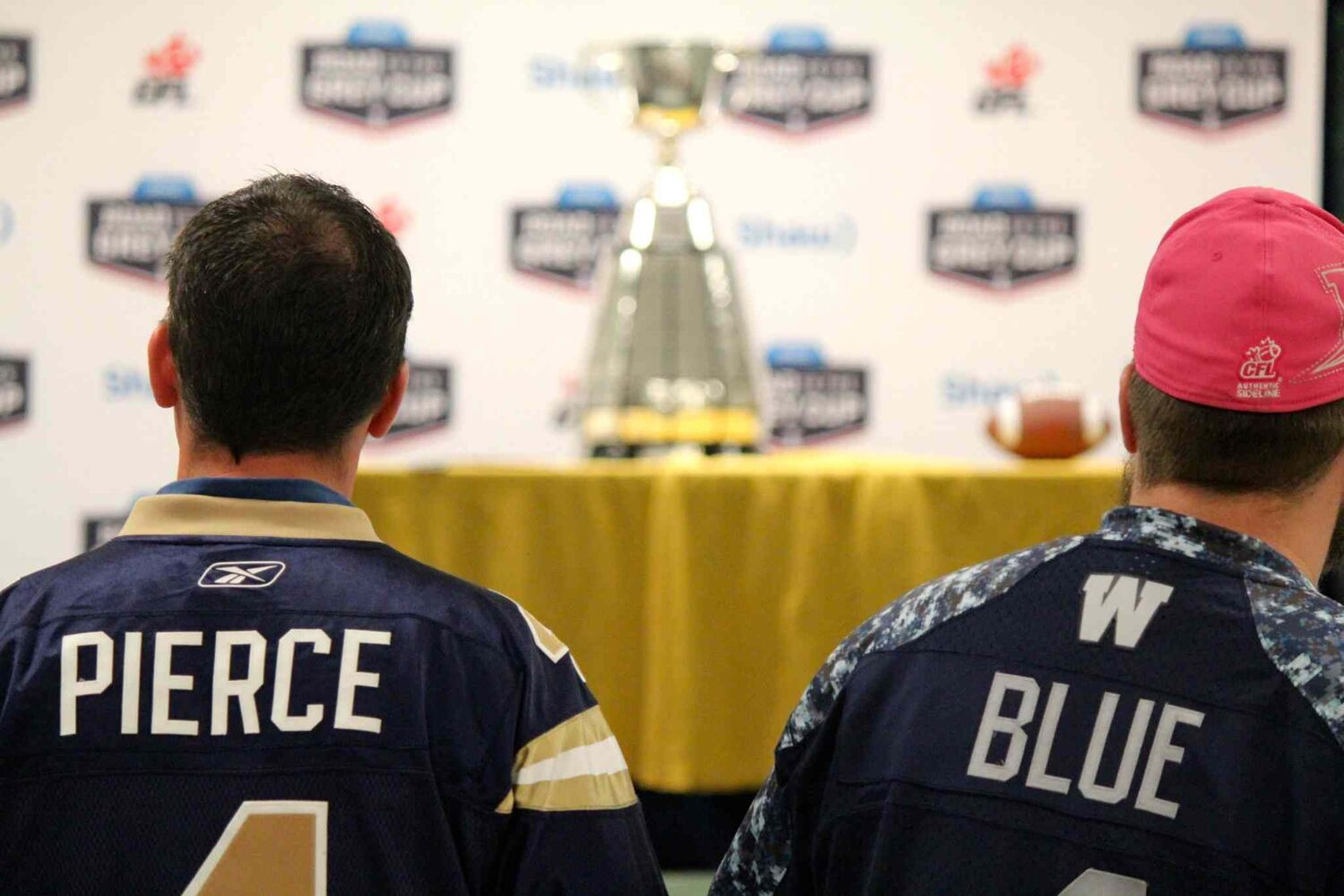 Two Bombers fans gaze at the Grey Cup from a distance in an event at The Pas. The trophy was in town as part of an eight-day tour through northern Manitoba to help promote the Grey Cup game in Winnipeg this year. (Jeff Hamilton / Winnipeg Free Press)