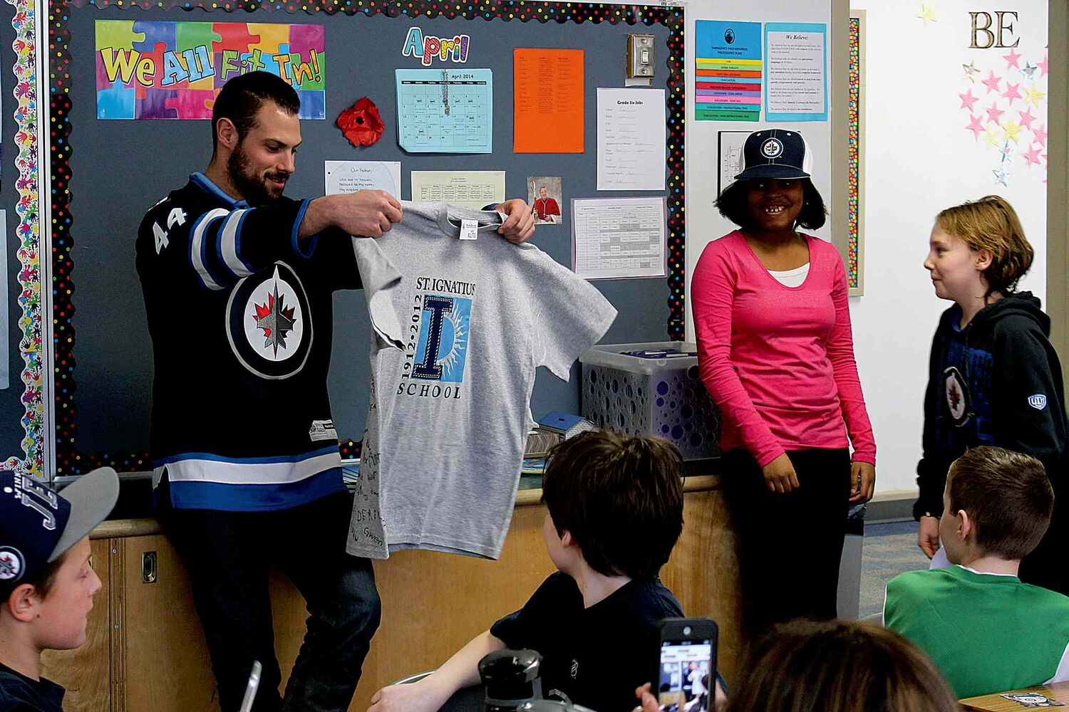 Winnipeg Jets defenceman Zach Bogosian checks out a t-shirt presented to him by a class of sixth grade students. Bogosian paid a visit to students at St. Ignatius School as a reward for winning the Classroom Recycling Challenge.