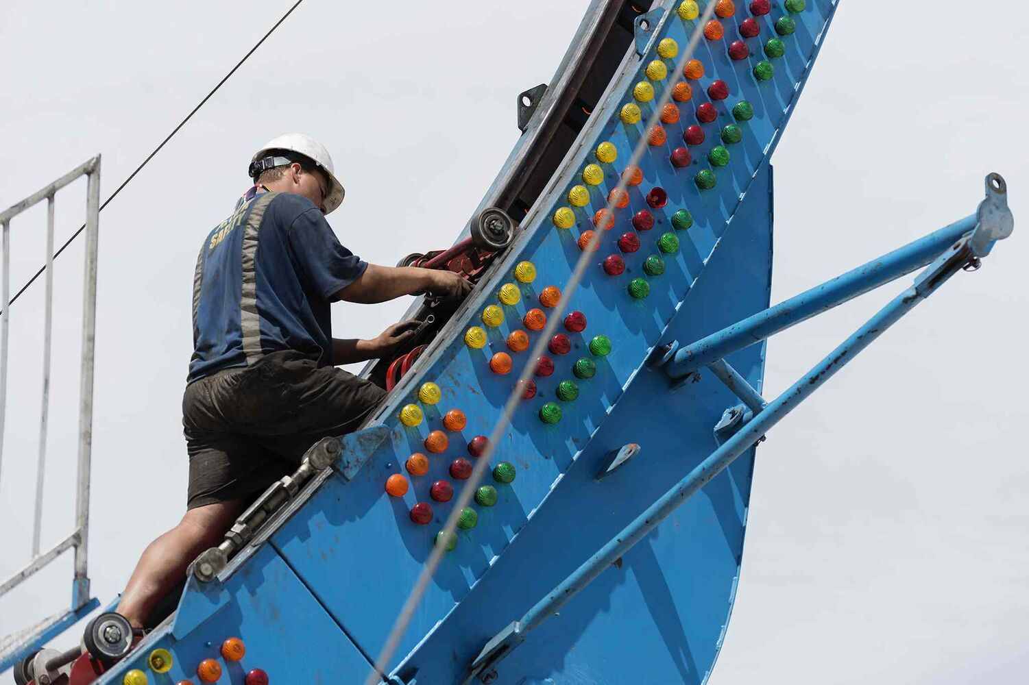 Roan Van Der Westhuizen works on preparing the Fire Ball ride at the Red River Ex before opening day June 13. (Sarah Taylor / Winnipeg Free Press)