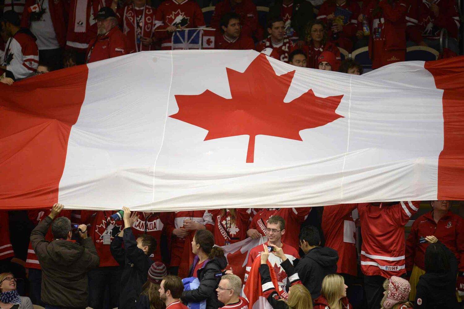Fans hold up a Canadian flag at the IIHF World Junior Hockey Championship game again the United States Tuesday. (Frank Gunn / The Canadian Press)