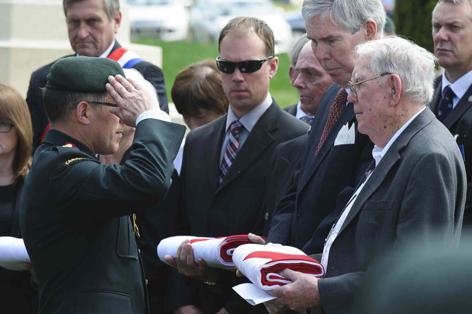 Colonel Guy Maillet, the Canadian Defence Attache Paris, salutes Clifford Teague, nephew of Lieutenant Clifford Neelands, at the burial of eight Canadian First World War soldiers from the 78th Battalion at the Caix British Cemetery in Caix, France on 13 May 2015  as part of the largest single find of unknown Canadian soldiers since the Canadian Armed Forces Casualty Identification program started in 2006. (Corporal Jordan Lobb, Canadian Forces Joint Imagery Center, Ottawa)