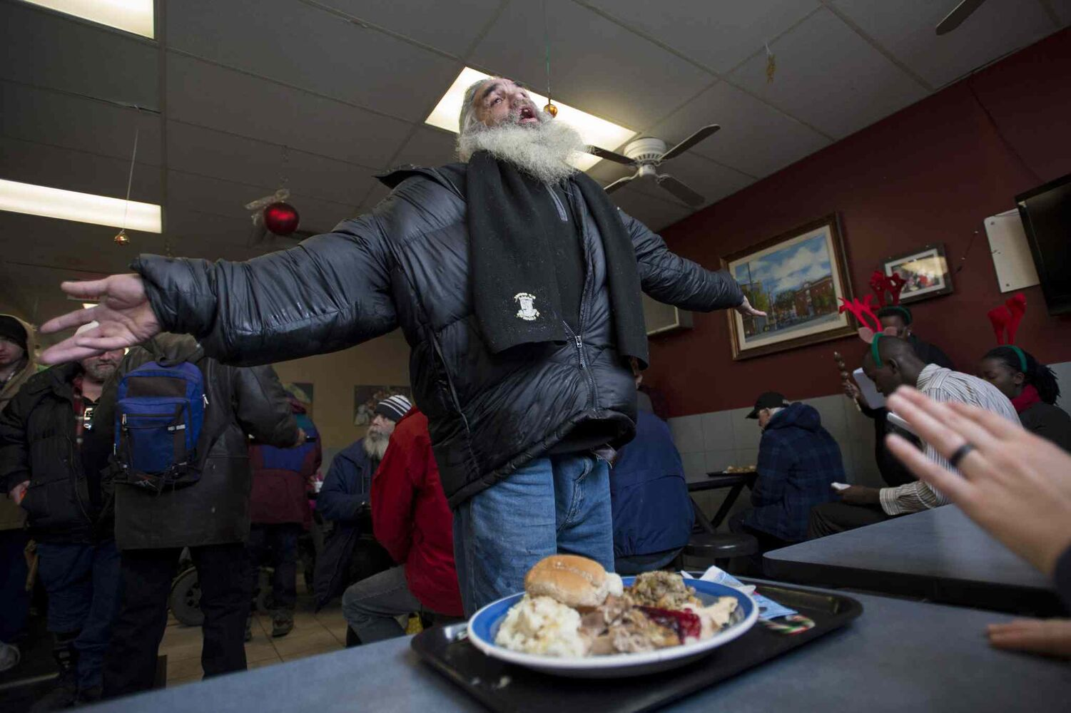 Moses Gibson dances to choir songs after receiving his Christmas Day lunch at the Shepherds of Good Hope in Ottawa. (The Canadian Press)