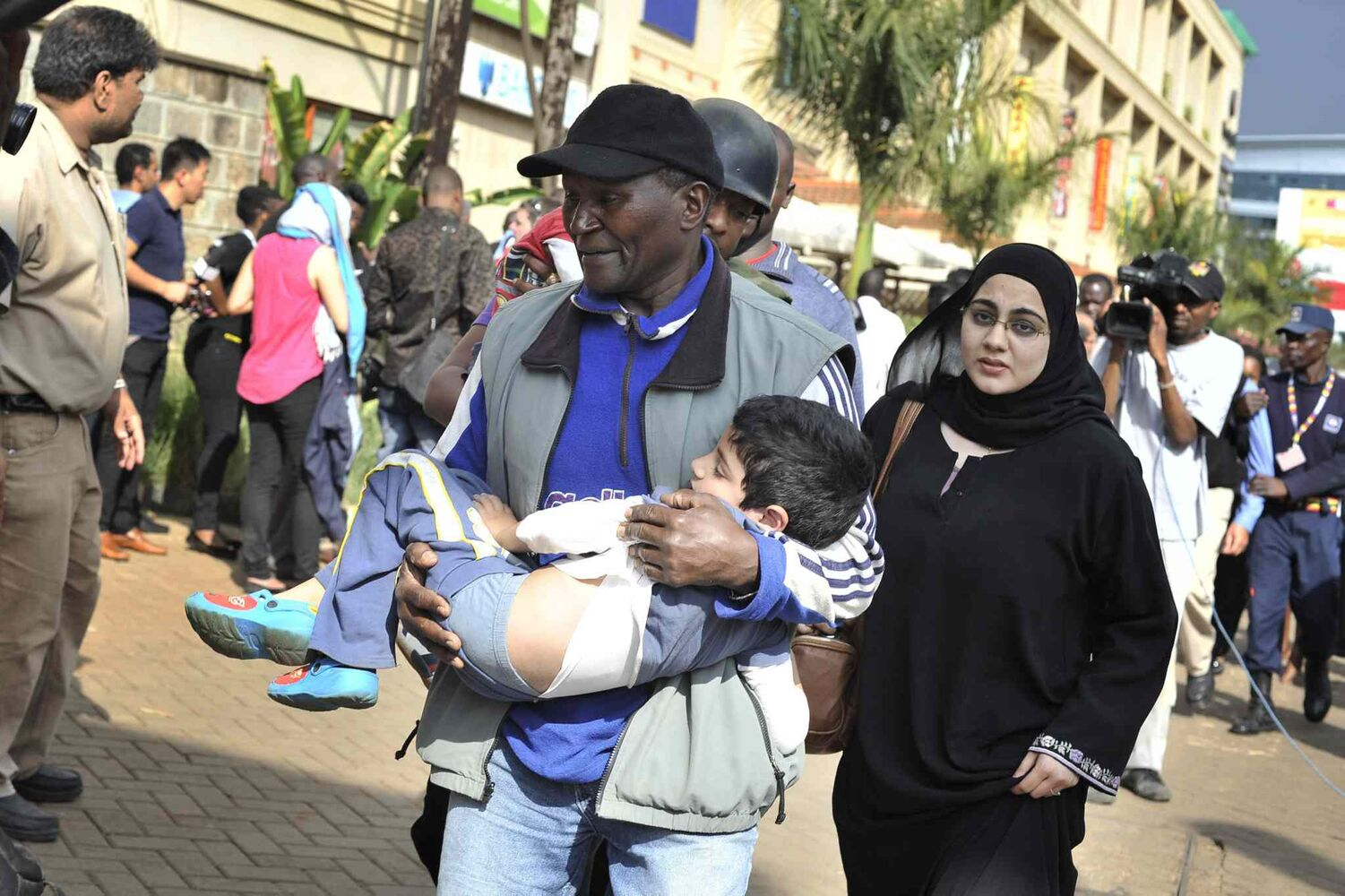 A rescue worker helps a child outside the Westgate Mall in Nairobi, Kenya, Saturday, after gunmen threw grenades and opened fire during an attack that left multiple dead and dozens wounded. A witness to the attacks on the upscale shopping mall says that gunmen told Muslims to stand up and leave and that non-Muslims would be targeted.  (Riccardo Gangale / The Associated Press)