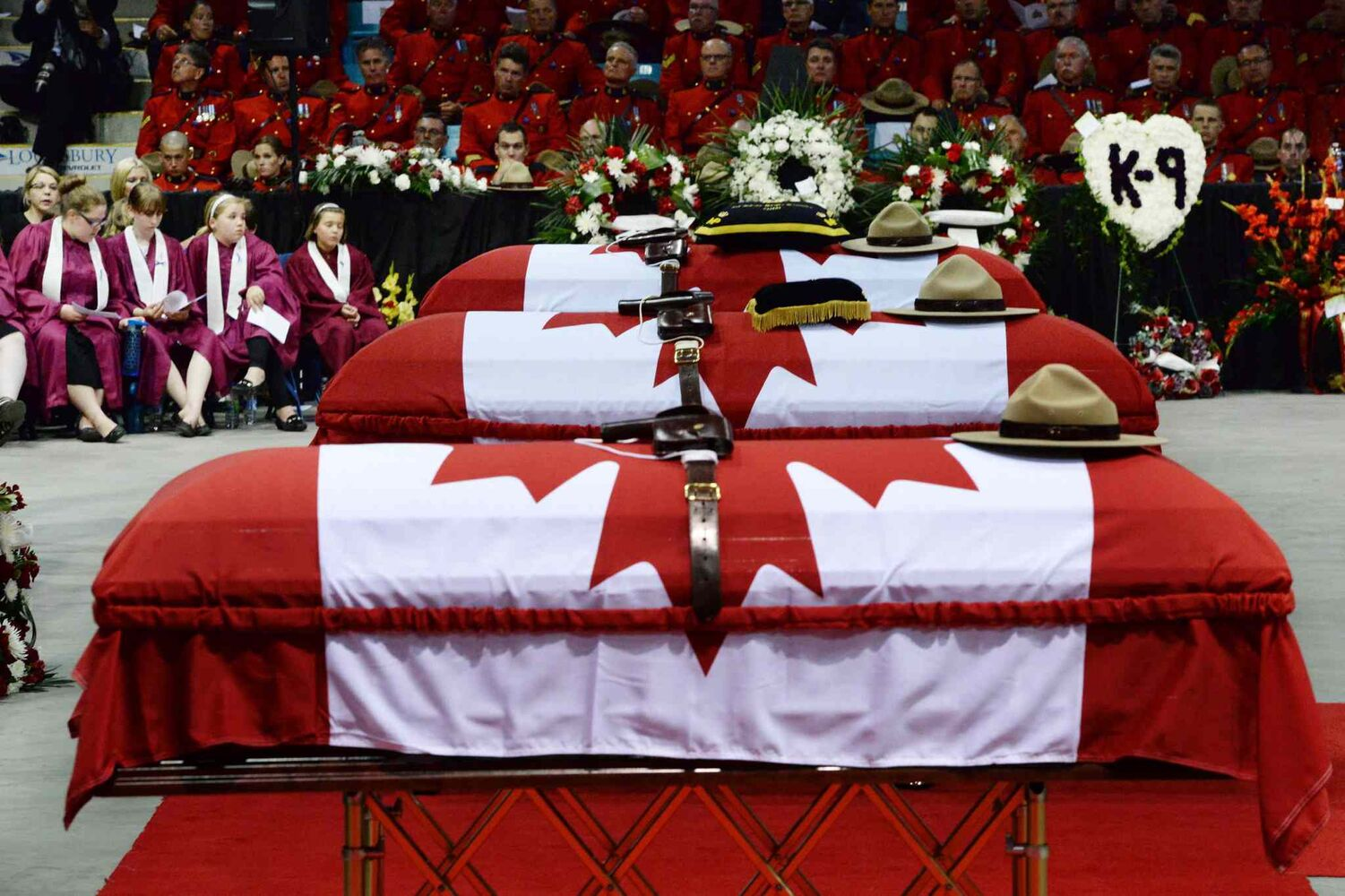 Stetsons rest on the caskets of the three slain RCMP officers, Const Dave Ross, Const. Douglas Larche and Const. Fabrice Gevaudan. (Sean Kilpatrick / The Canadian Press)