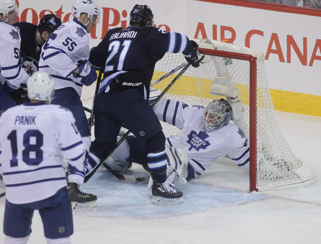 Toronto Maple Leafs goaltender James Reimer (34) manages to deflect the puck from going in the net during the first period Saturday. (Ruth Bonneville / Winnipeg Free Press)