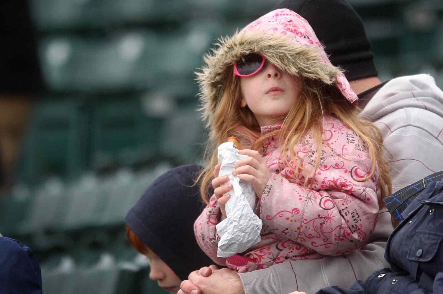 Saturday's weather turned out to be well below average seasonal temperatures, but that didn't stop a young girl in a fur-trimmed coat from enjoying a promised hotdog while watching the Goldeyes on the field. (Ruth Bonneville / Winnipeg Free Press)