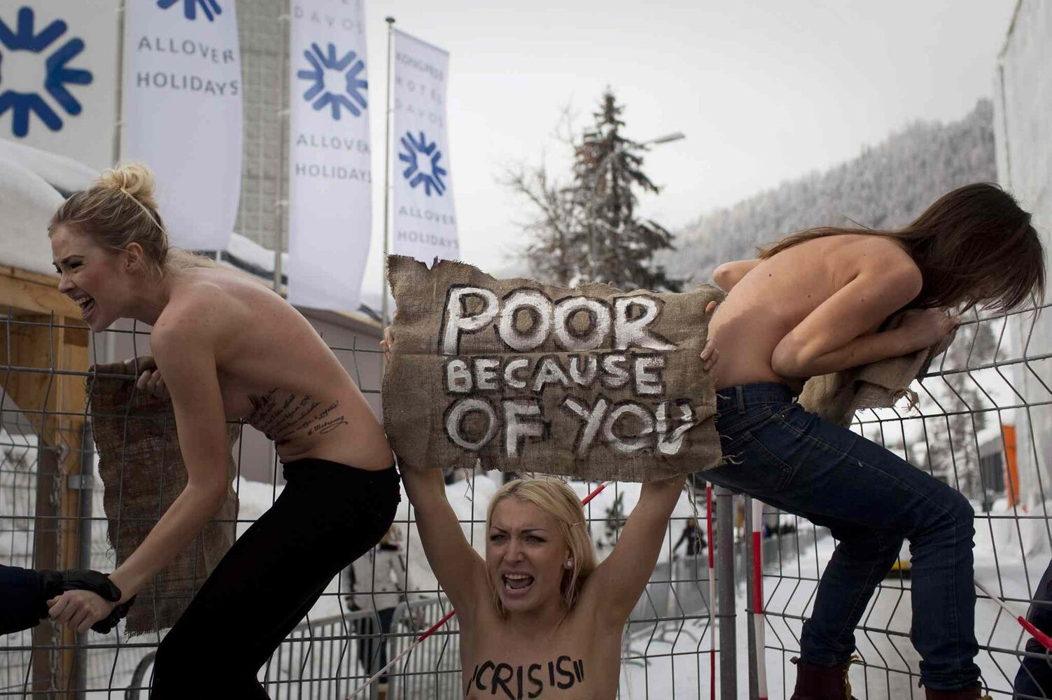 Jan. 28, 2012: Topless Ukrainian protesters climb up a fence at the entrance to the congress center where the World Economic Forum takes place in Davos, Switzerland. (Anja Niedringhaus / The Associated Press)