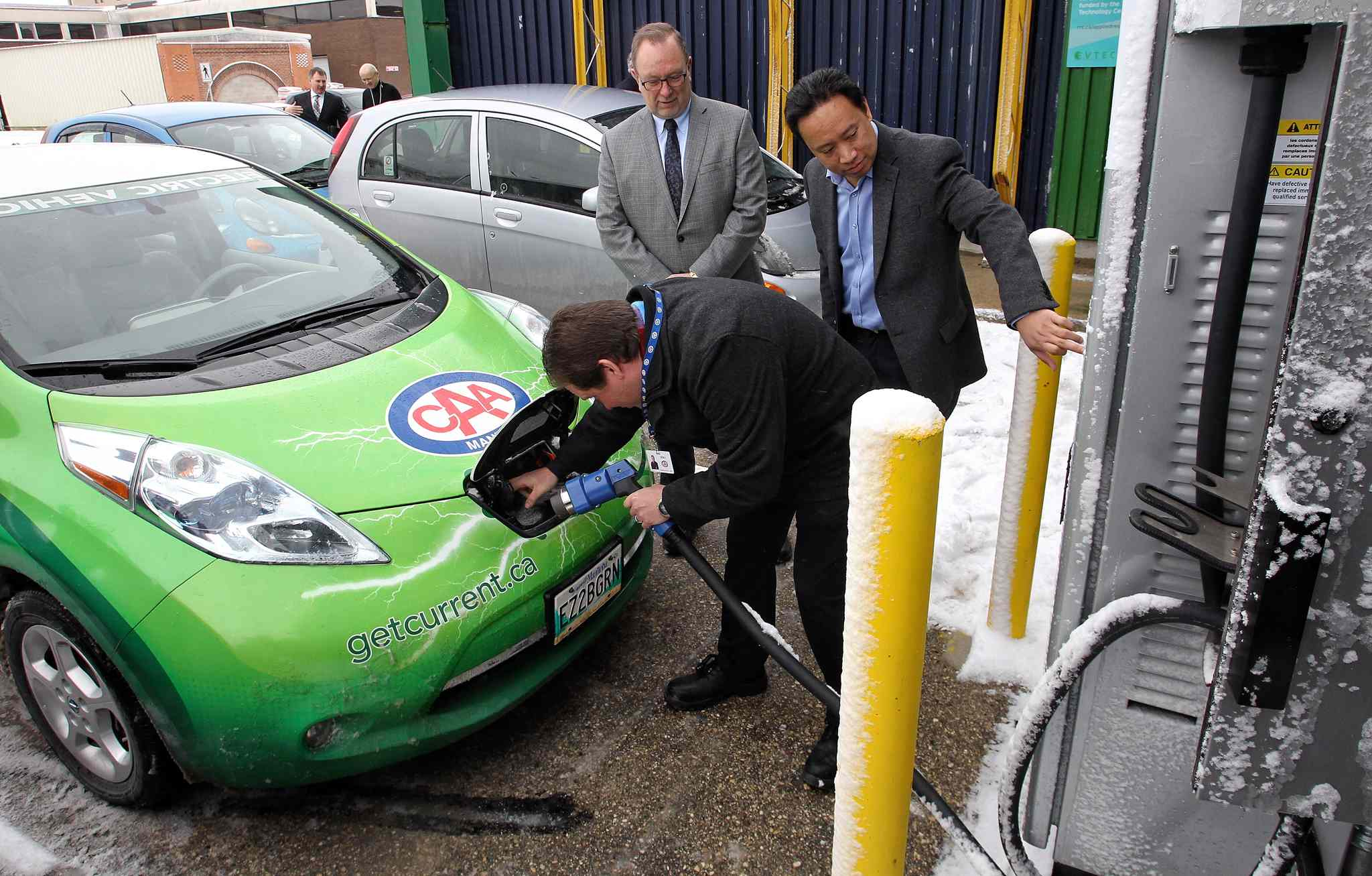 Ken Francis with CAA Manitoba plugs in his car while Jose Reyes (right), the research manager at RRC, and Ray Hoemsen, Director of Applied Research at RRC, help out after the unveiling of the recently installed Level 3 electric vehicle quick charging station at the RRC Notre Dame campus.